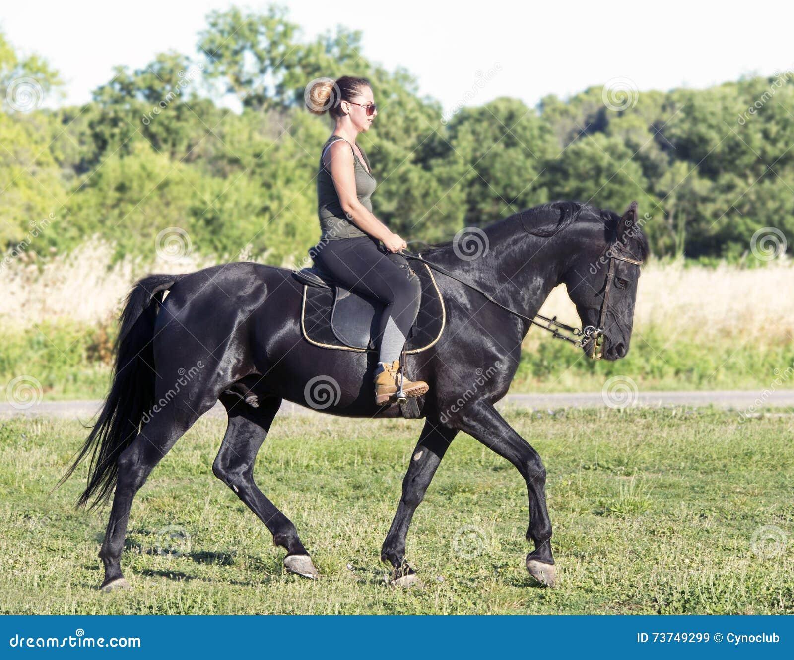 Ragazza di guida sullo stallone nero