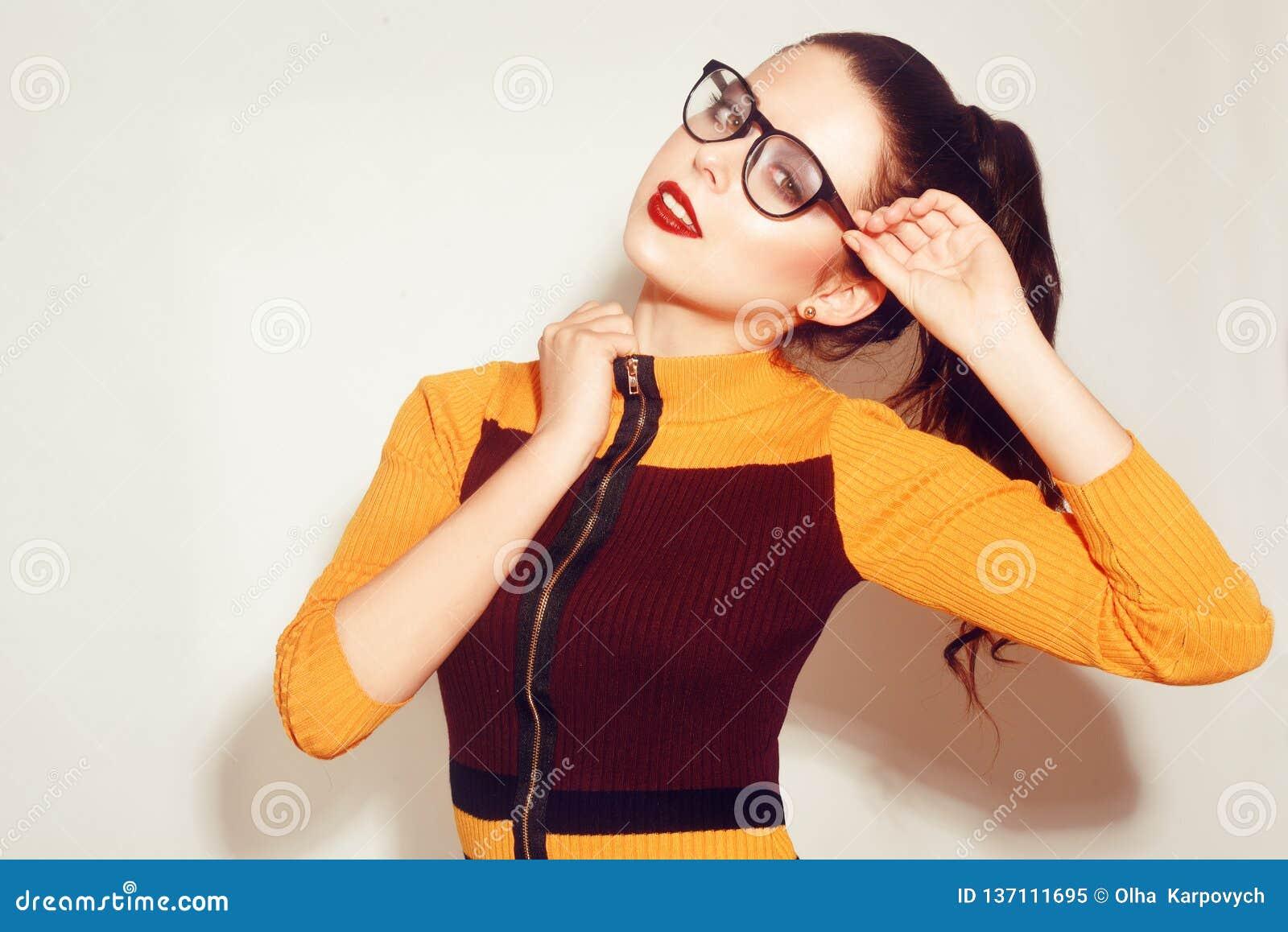 Ragazza di modello castana di modo di bellezza che indossa i vetri alla moda Donna sexy con trucco perfetto, il vestito arancio e