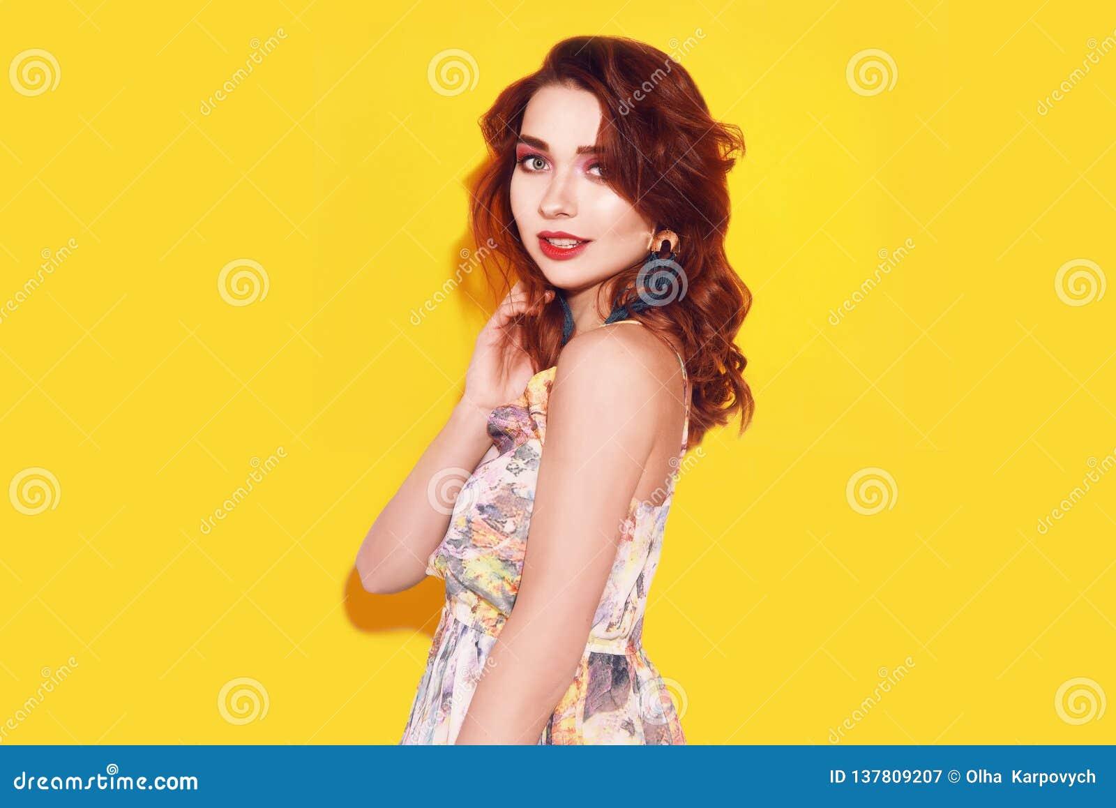 Ragazza di modo in vestito sul ballare giallo del fondo La ragazza graziosa con capelli lungamente cerly volanti ed il rosa compo