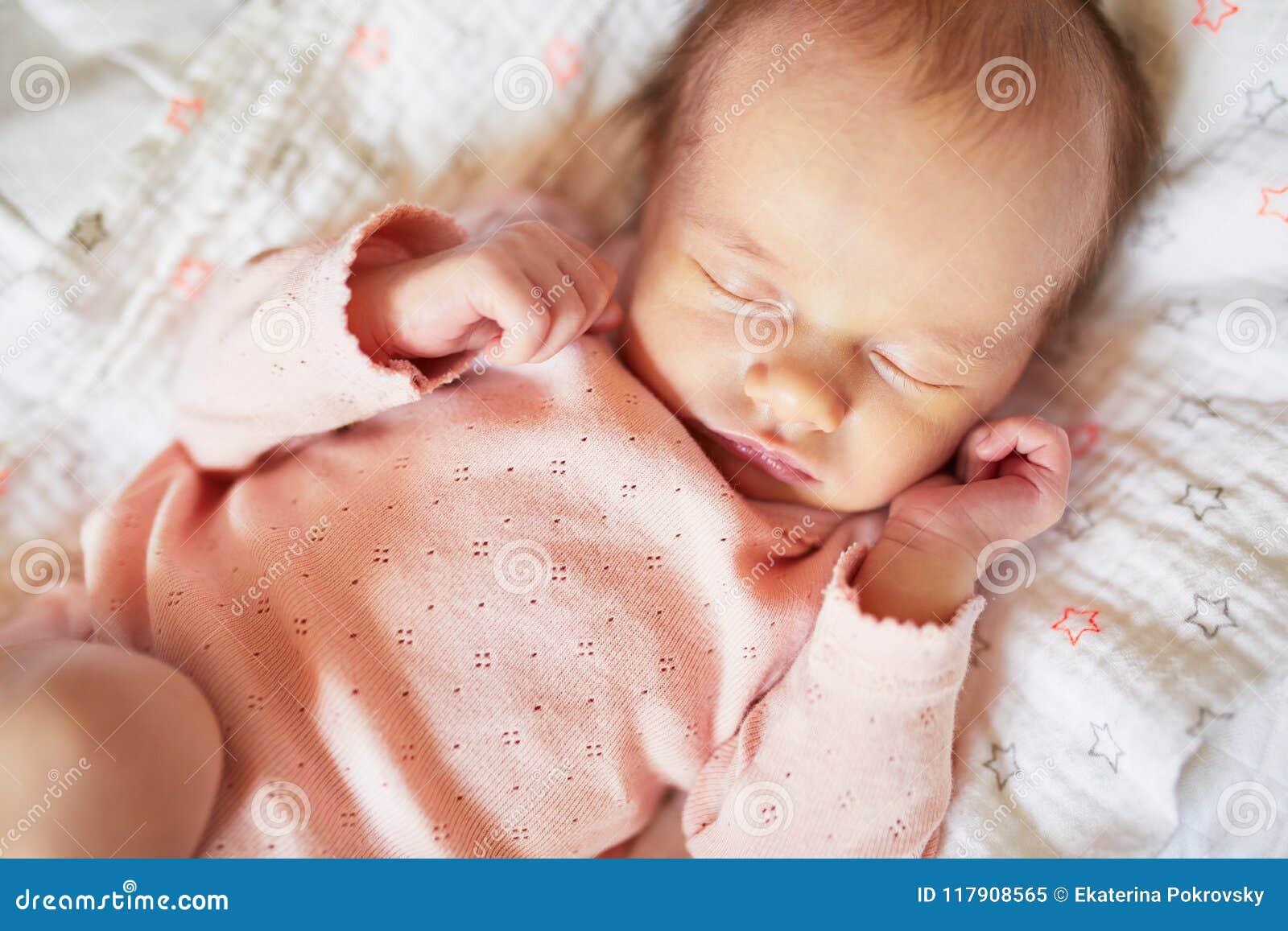 Ragazza di neonato che dorme in sua greppia