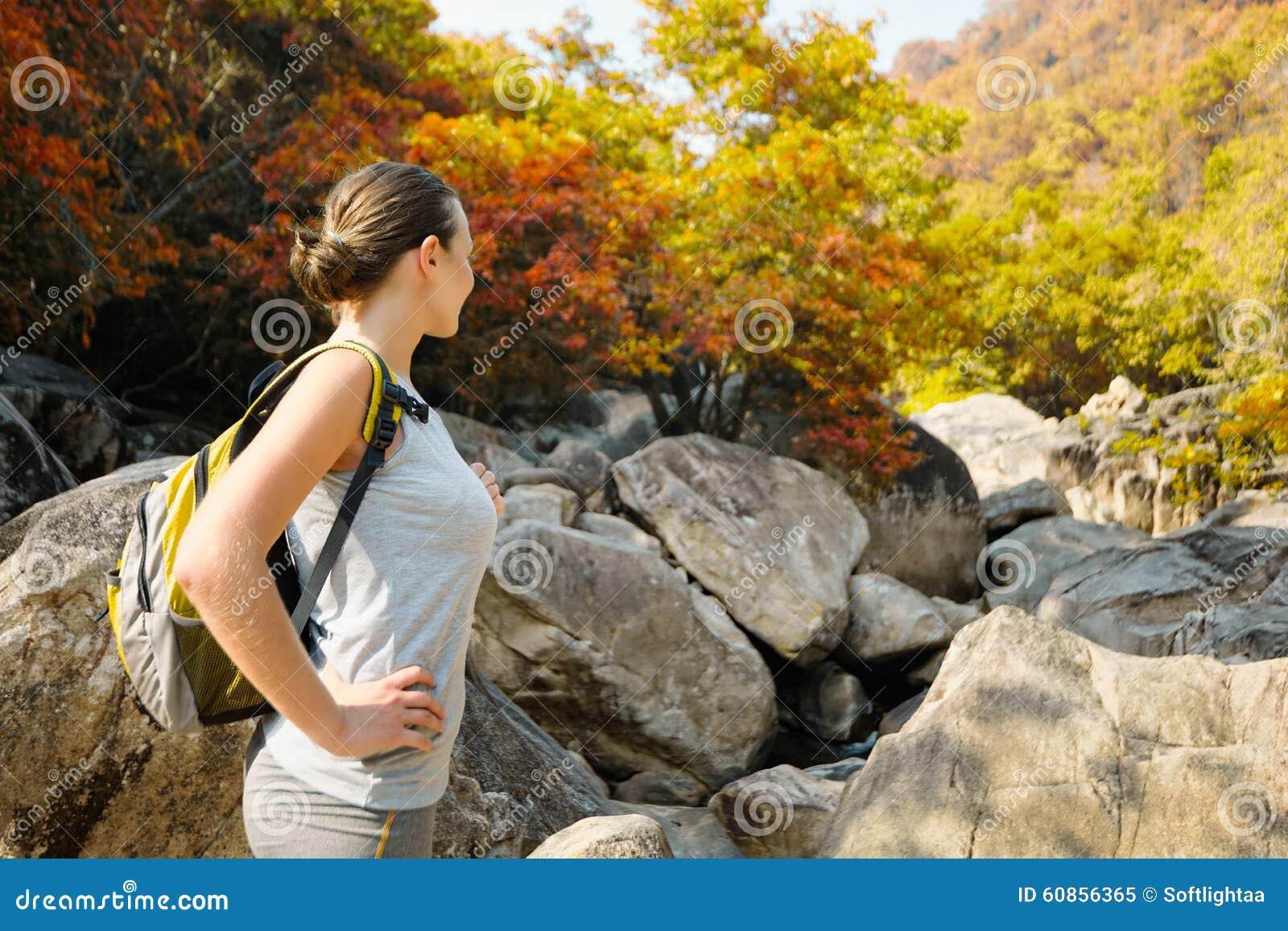 Ragazza di viaggio con lo zaino in autunno delle montagne