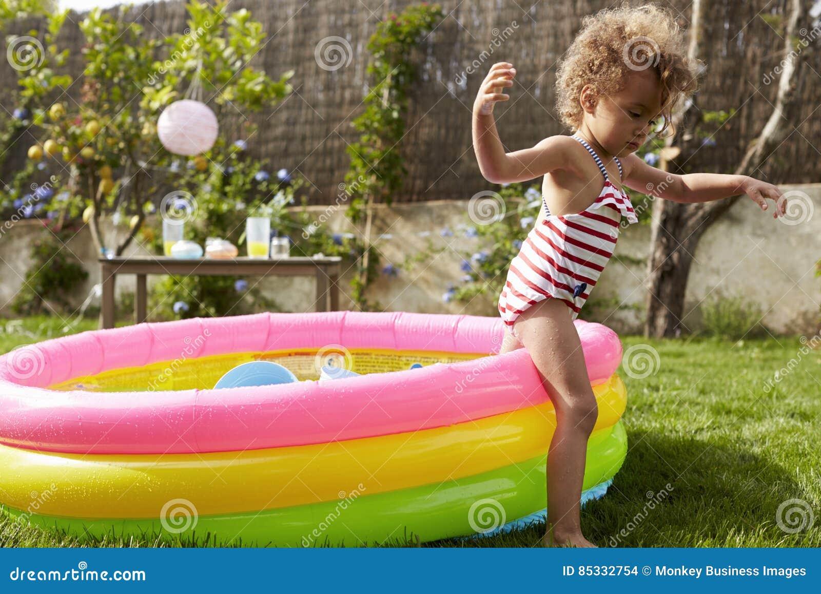 Ragazza divertendosi nella piscina per bambini del giardino