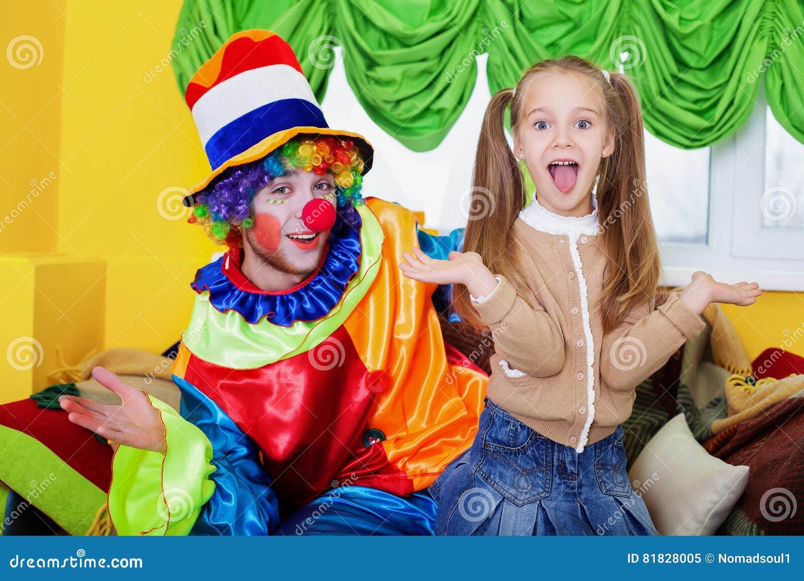 Ragazza e pagliaccio del bambino che giocano sulla festa di compleanno