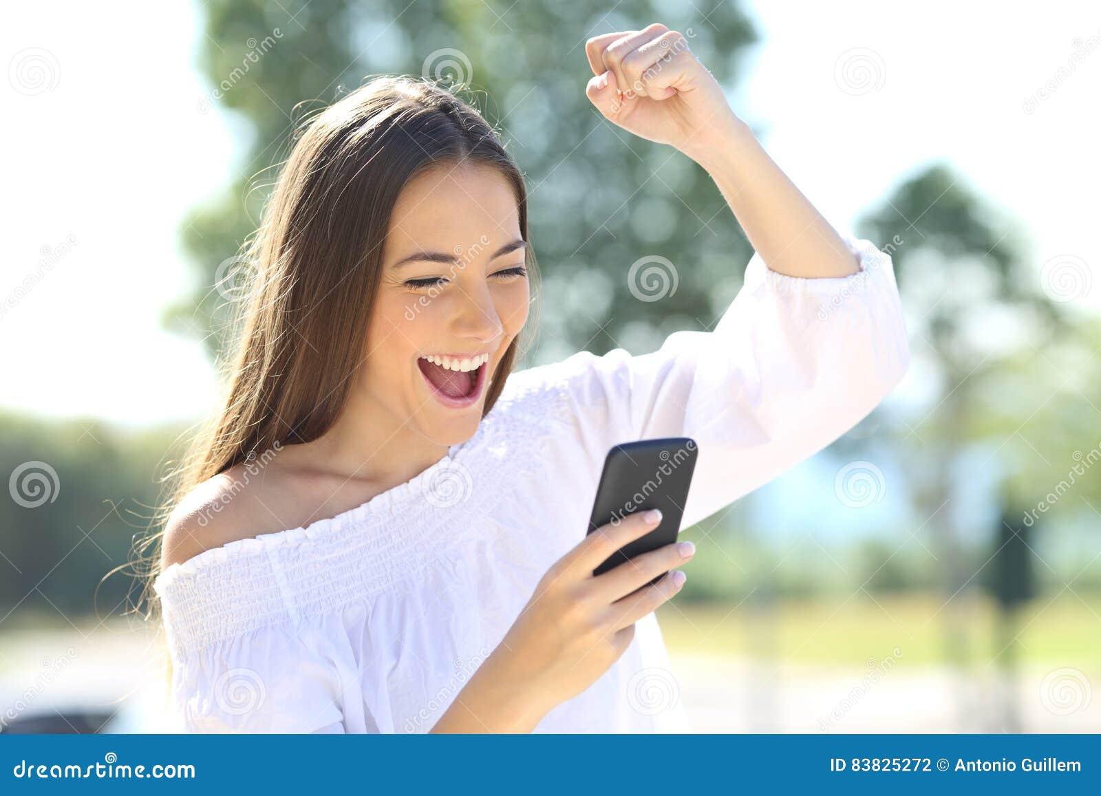 Ragazza emozionante con un telefono cellulare in un parco