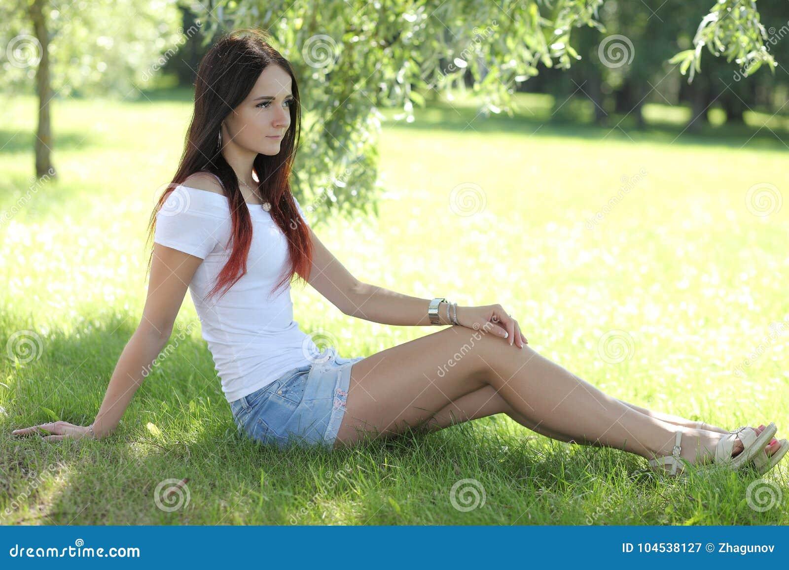Ragazza erotica con la mini gonna su erba verde
