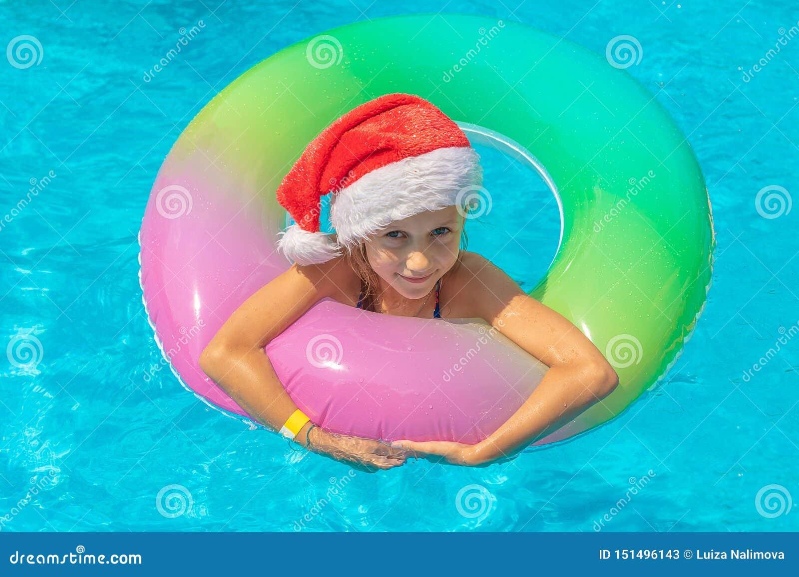 Ragazza felice che galleggia in uno stagno blu in cappelli di Santa su un fondo blu, sullo sguardo alla macchina fotografica e su