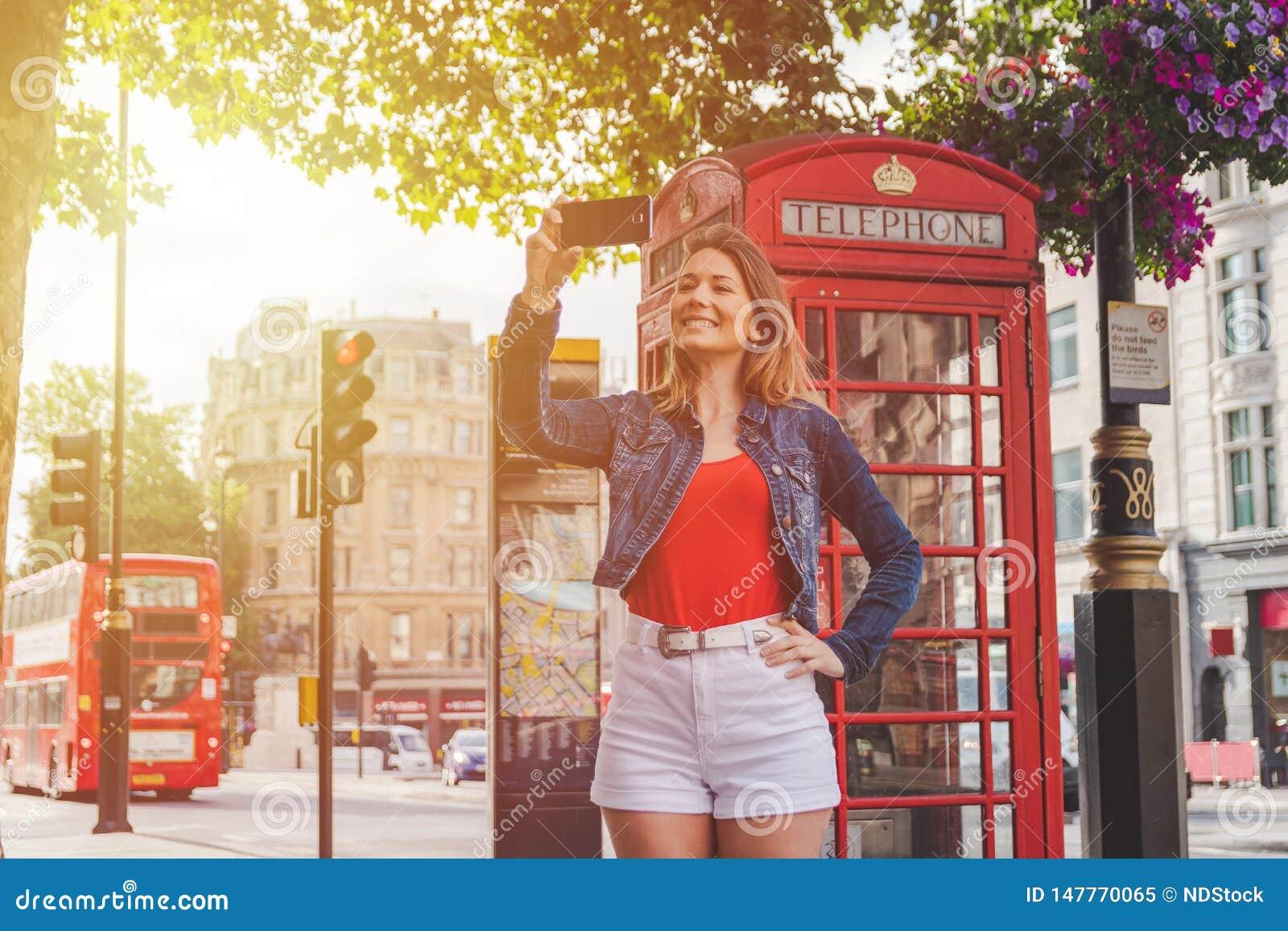 Ragazza felice che prende un selfie davanti ad un contenitore di telefono e ad un bus rosso a Londra