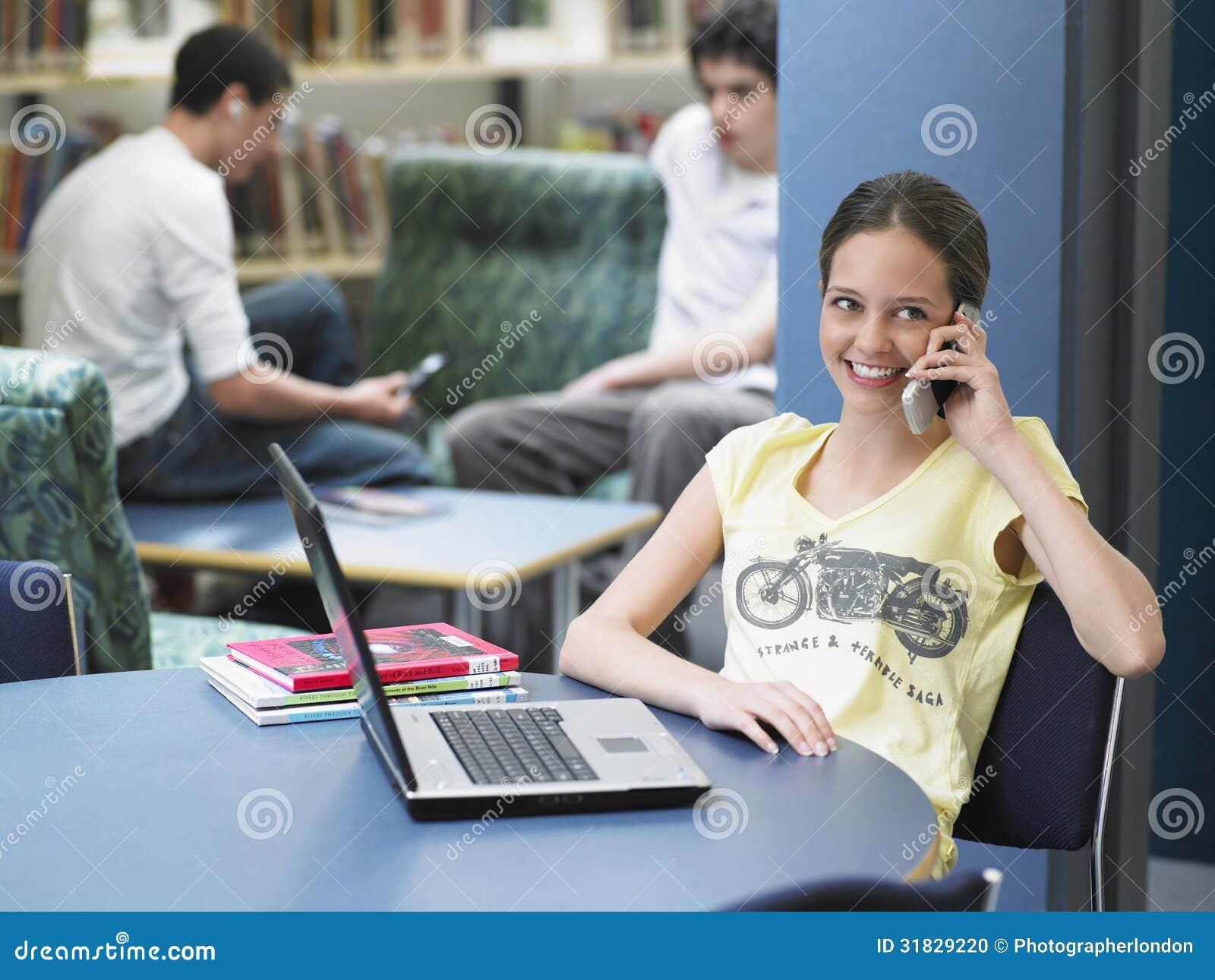 Ragazza felice che utilizza cellulare nella biblioteca