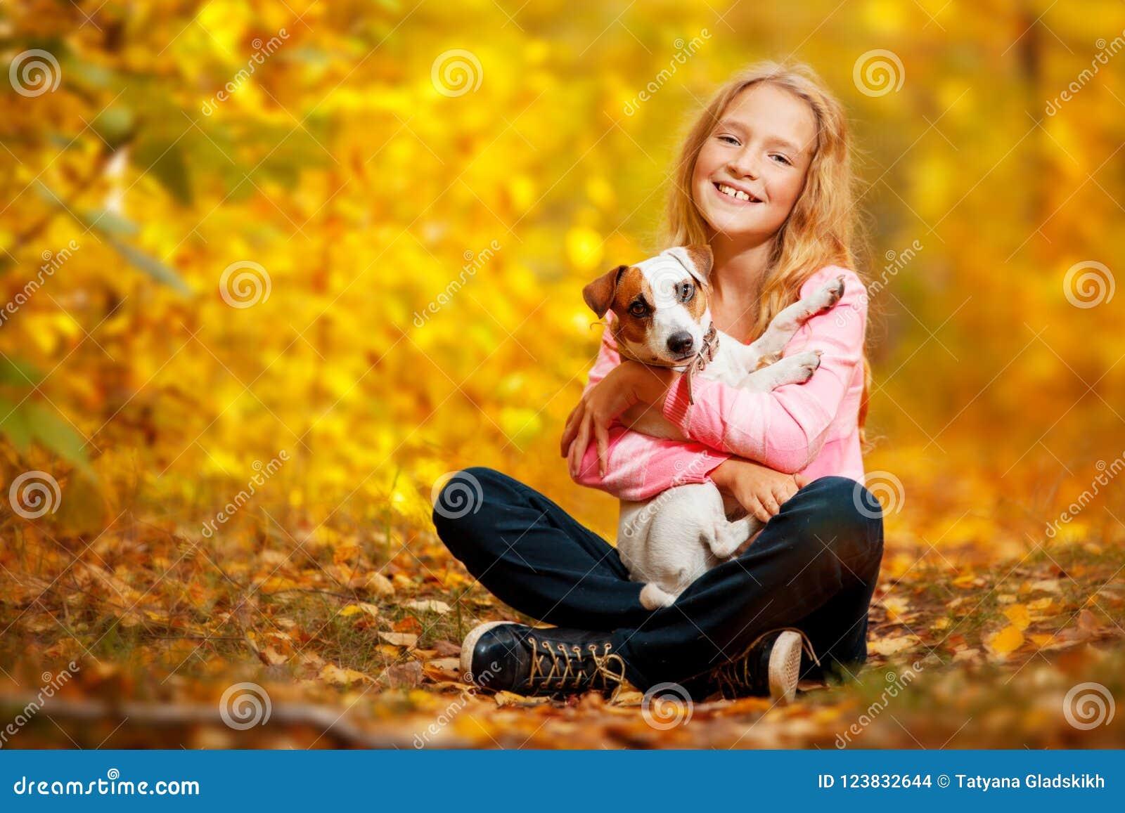 Ragazza felice con il cane all autunno