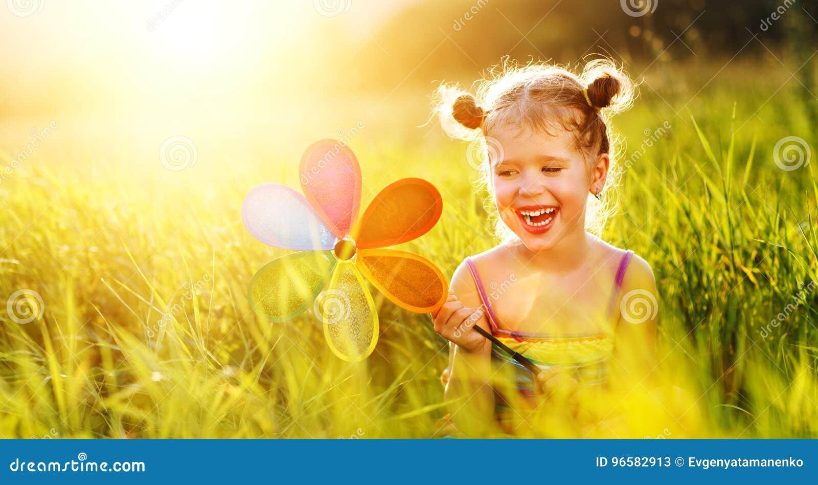 Ragazza felice del bambino con il mulino a vento variopinto della girandola di estate