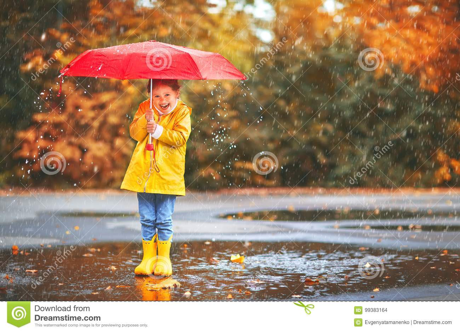 e58dd72b42741 La ragazza felice del bambino con un ombrello e gli stivali di gomma in  pozza su un autunno camminano