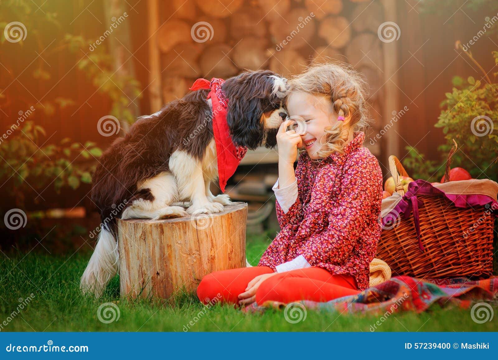 Ragazza felice del bambino divertendosi gioco con il suo cane nel giardino soleggiato di autunno