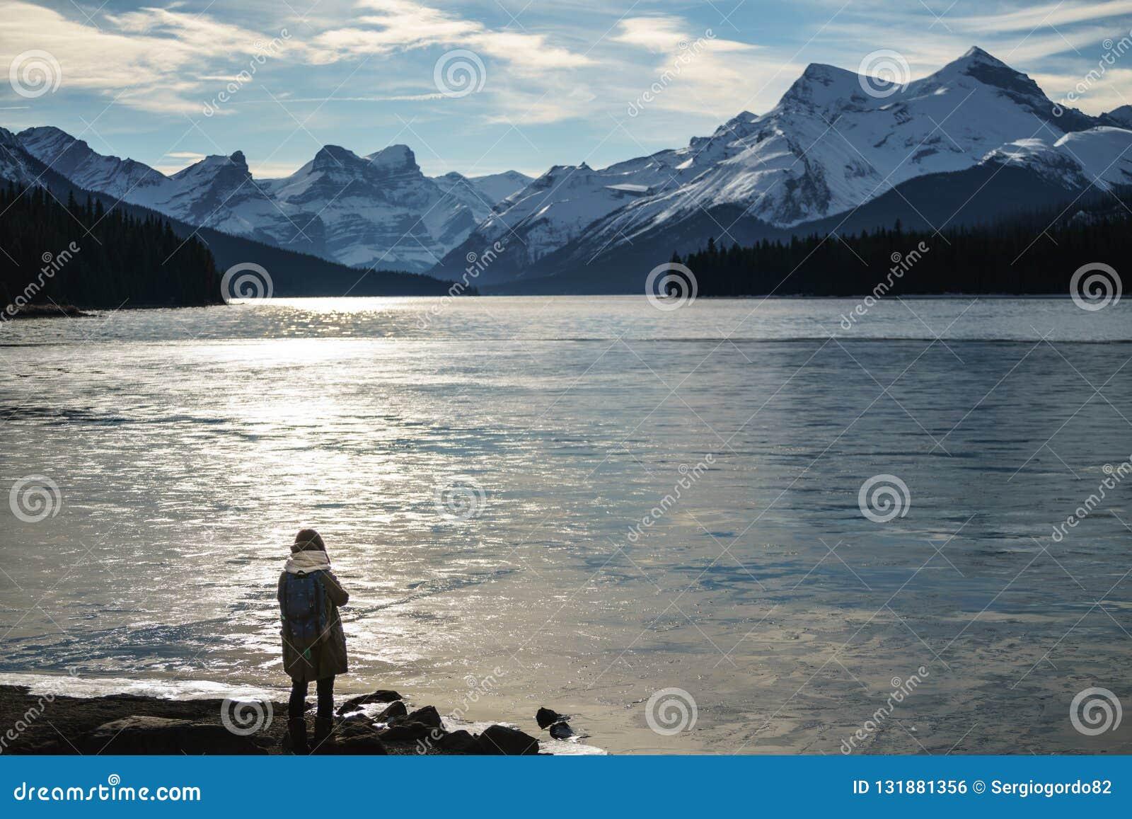 Ragazza fredda del lago del ghiaccio di mattina che guarda l orizzonte