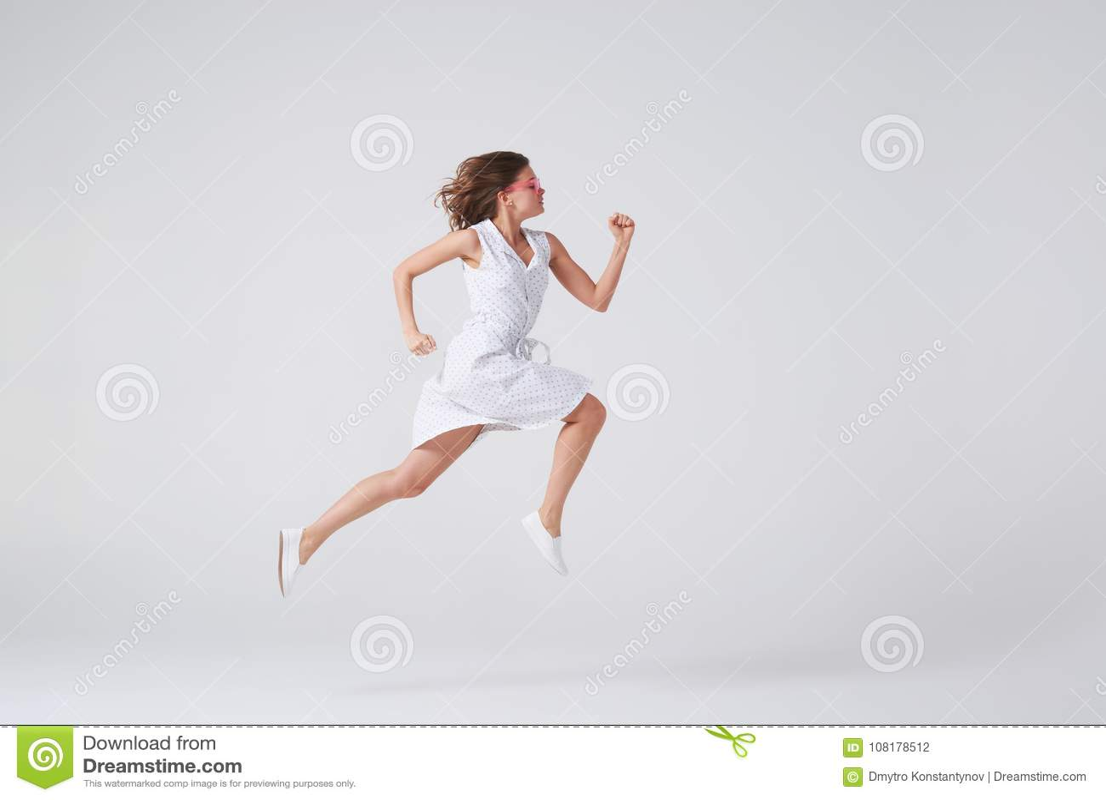 Ragazza gioiosa in vestito che salta su in aria sopra fondo in studio