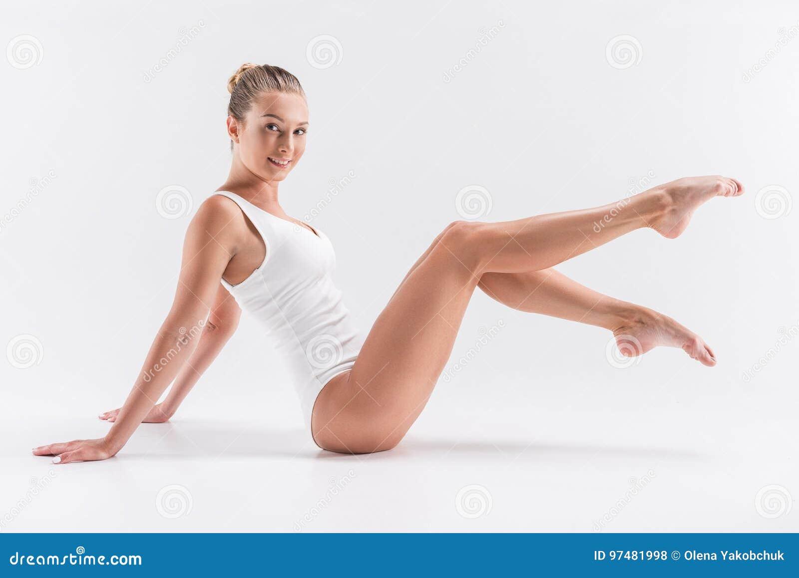 Ragazza giovanile di buon umore che pratica esercizio relativo alla ginnastica