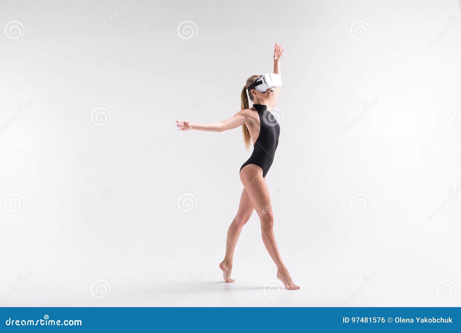 Ragazza giovanile seria che simula la composizione in sport facendo uso degli occhiali di protezione
