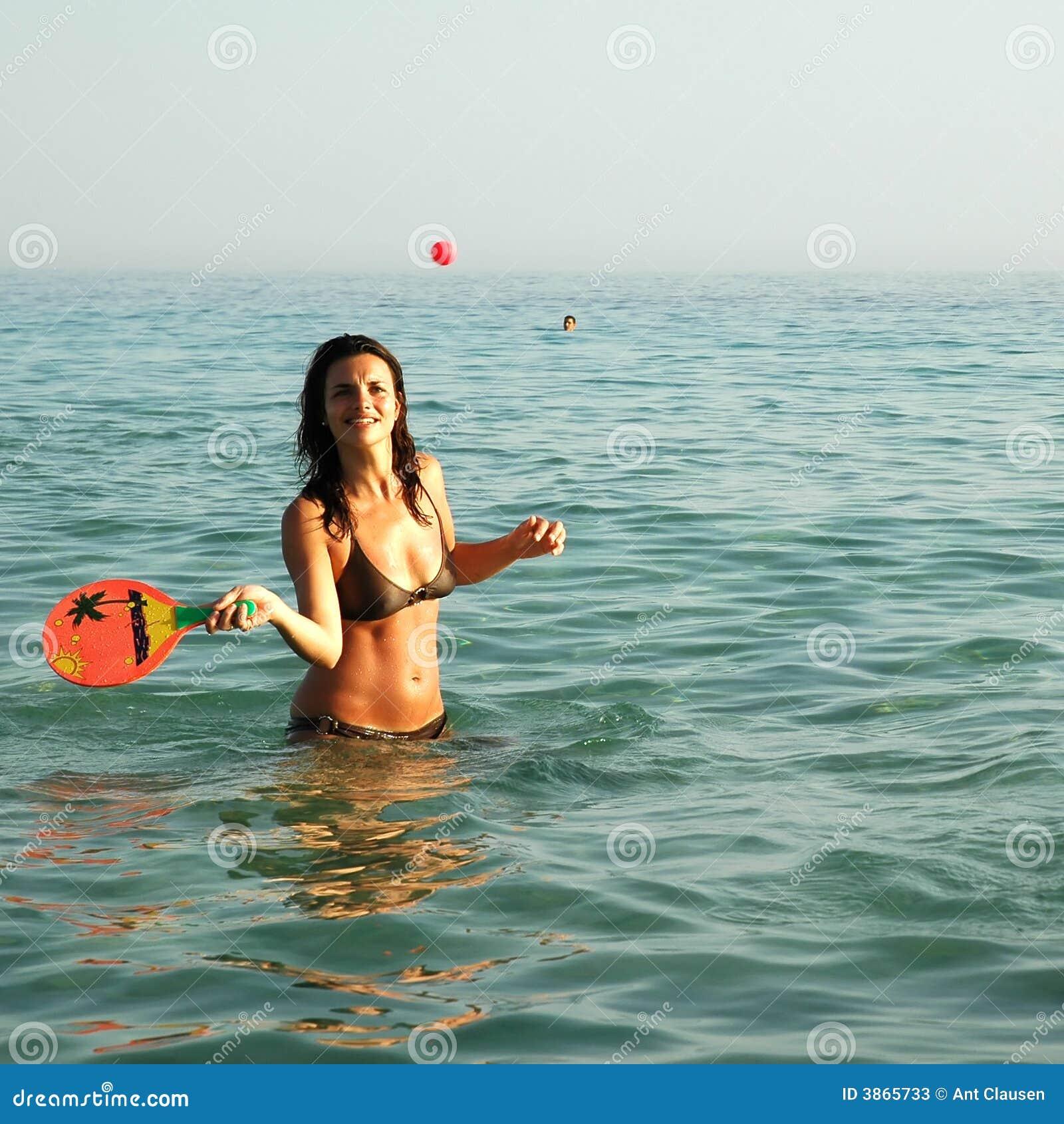 Ragazza graziosa che gioca sfera nell oceano