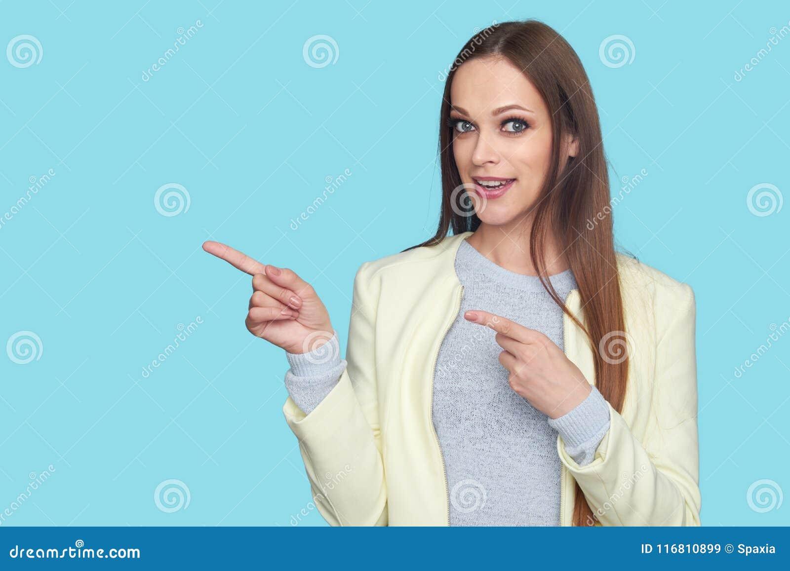 Ragazza graziosa che indica le dita lo spazio della copia