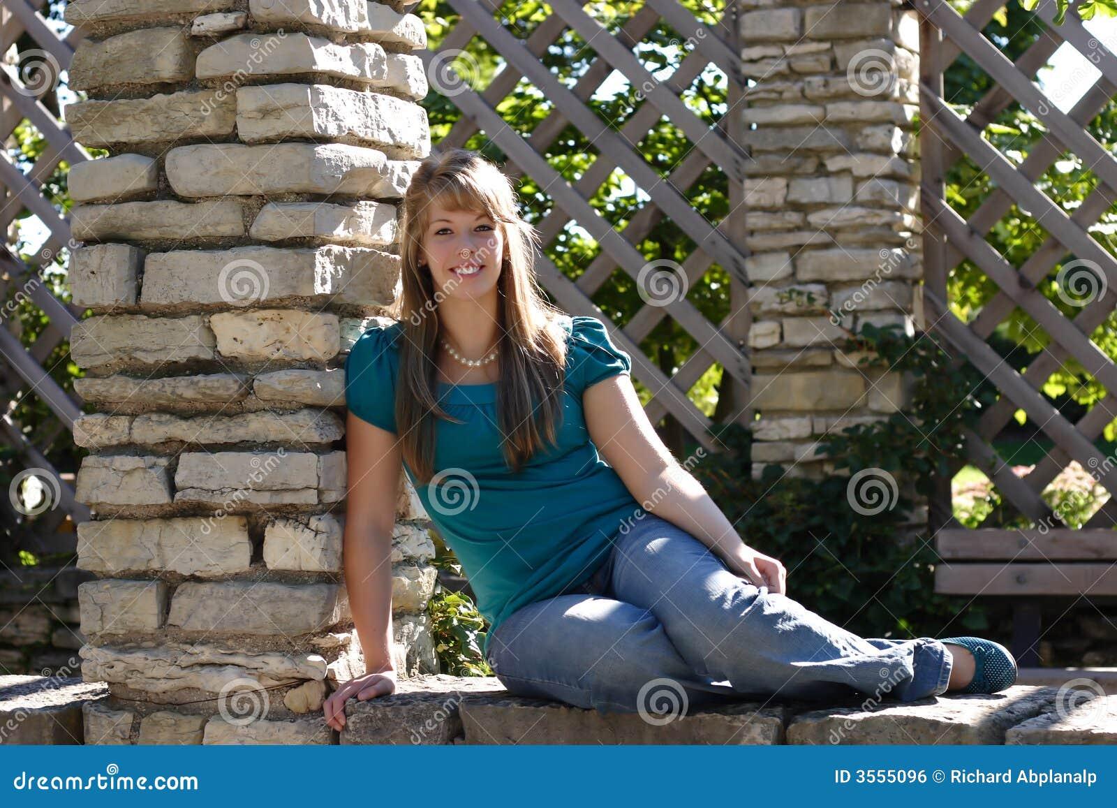 Ragazza graziosa che si siede su una parete