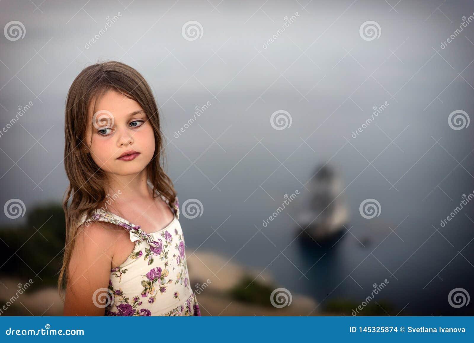 Ragazza graziosa in vestito da estate con i supporti bagnati dei capelli meditatamente dal mare
