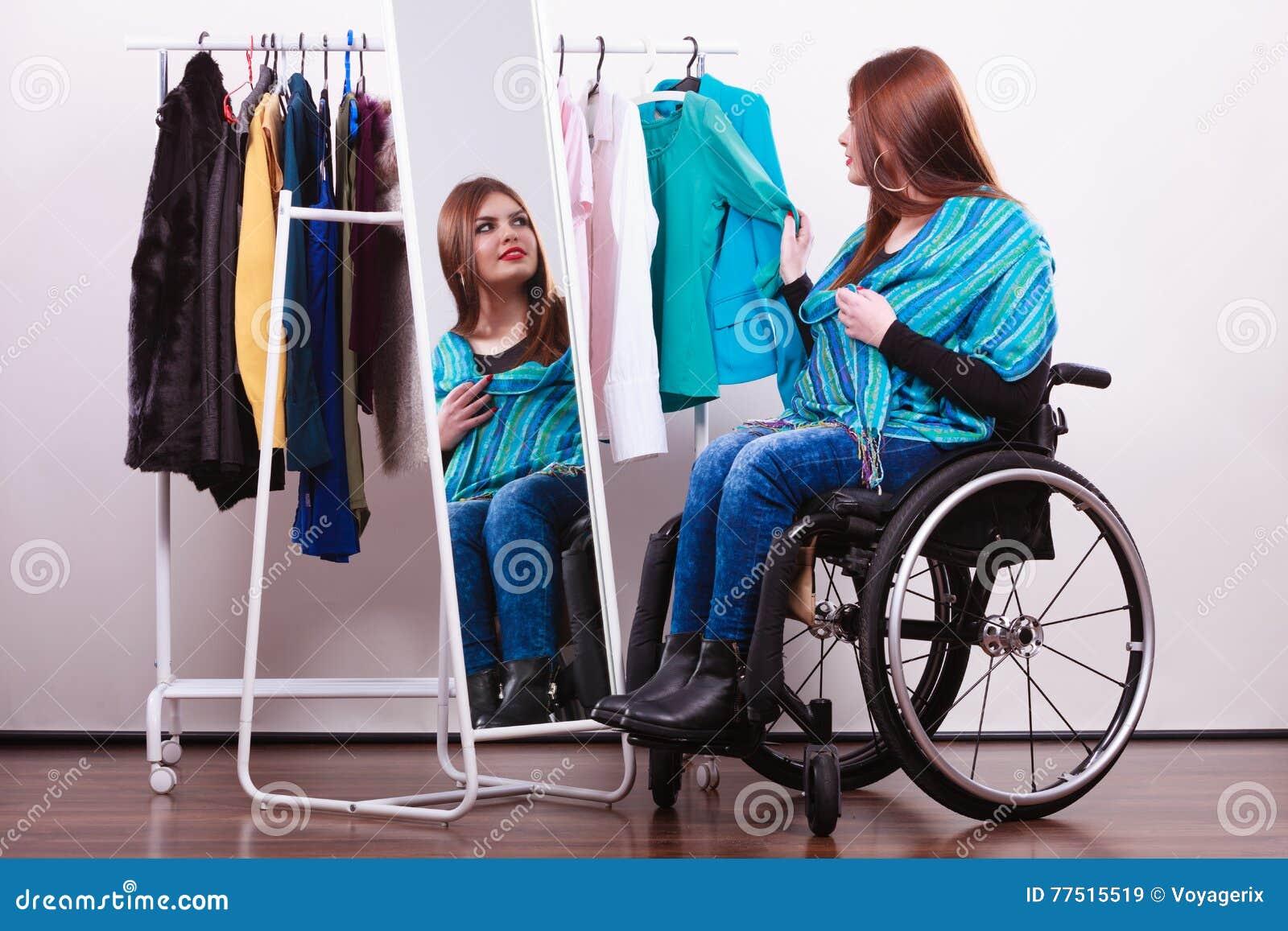 Ragazza handicappata sulla sedia a rotelle che sceglie i vestiti