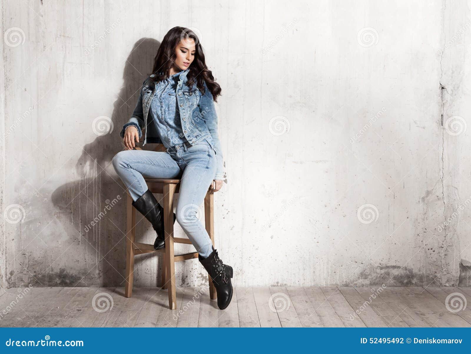 Ragazza in jeans che si siedono sulla sedia di legno