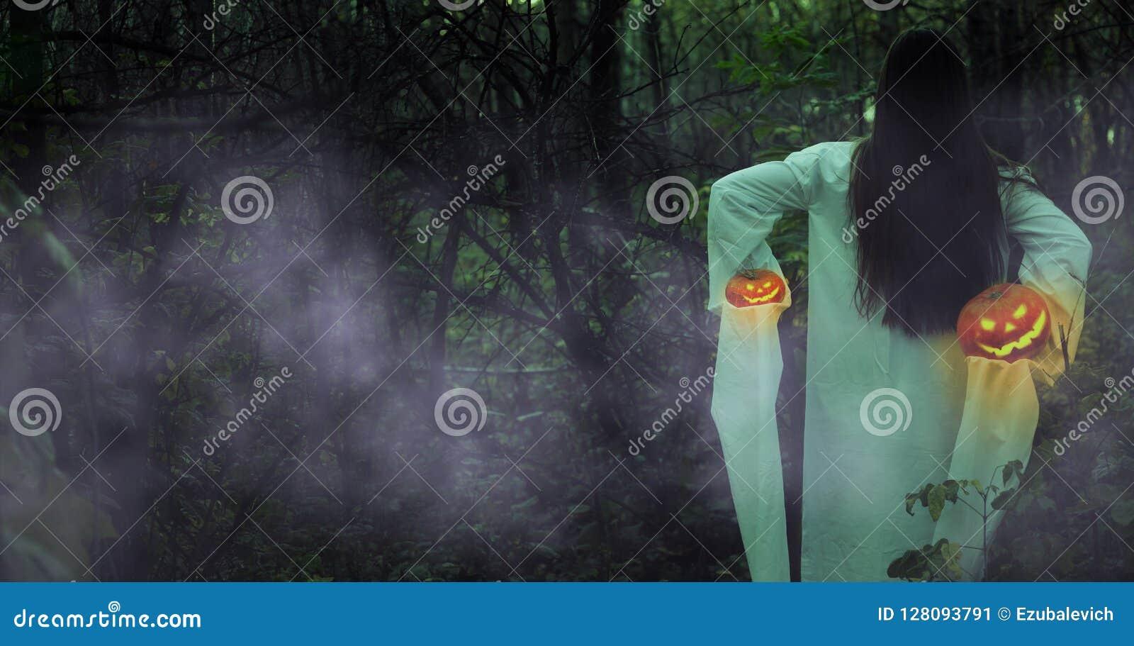 Ragazza morta con la Jack-o-lanterna in una foresta nebbiosa alla notte