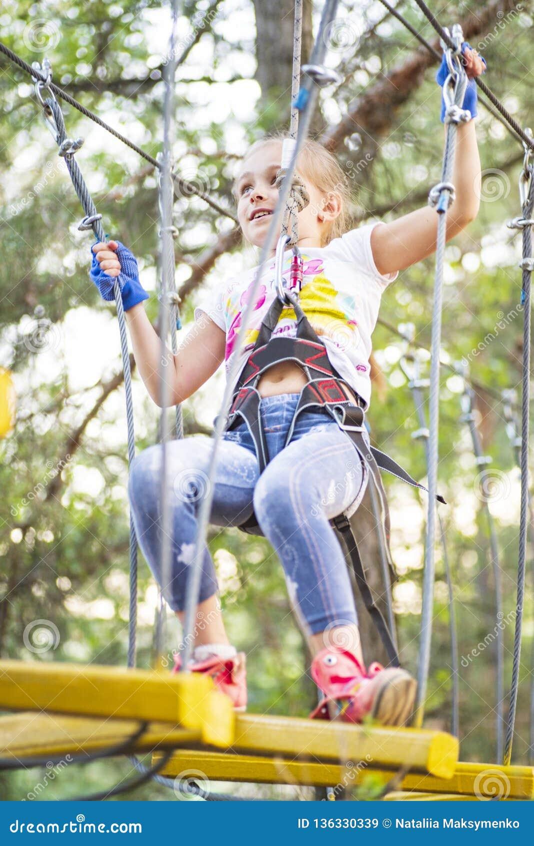 Ragazza negli ostacoli del passaggio del parco della corda, salita della ragazza la strada Parco della corda