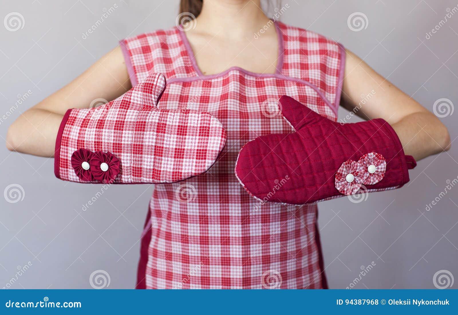 Ragazza nei guanti della cucina su fondo grigio