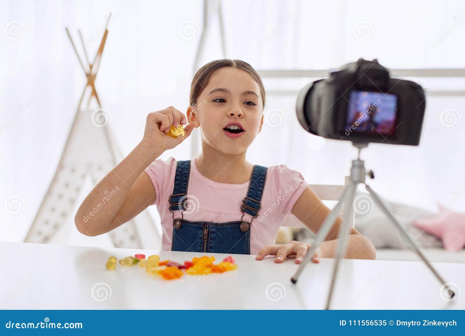 Ragazza ottimistica che parla del gusto delle caramelle gommose nel vlog