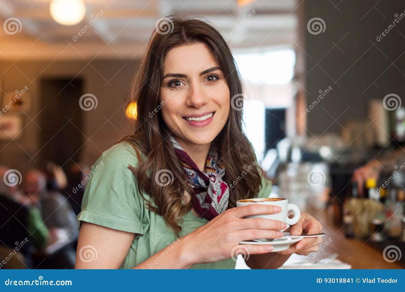 Ragazza positiva che prende una rottura che si siede alla barra nel negozio del caffè