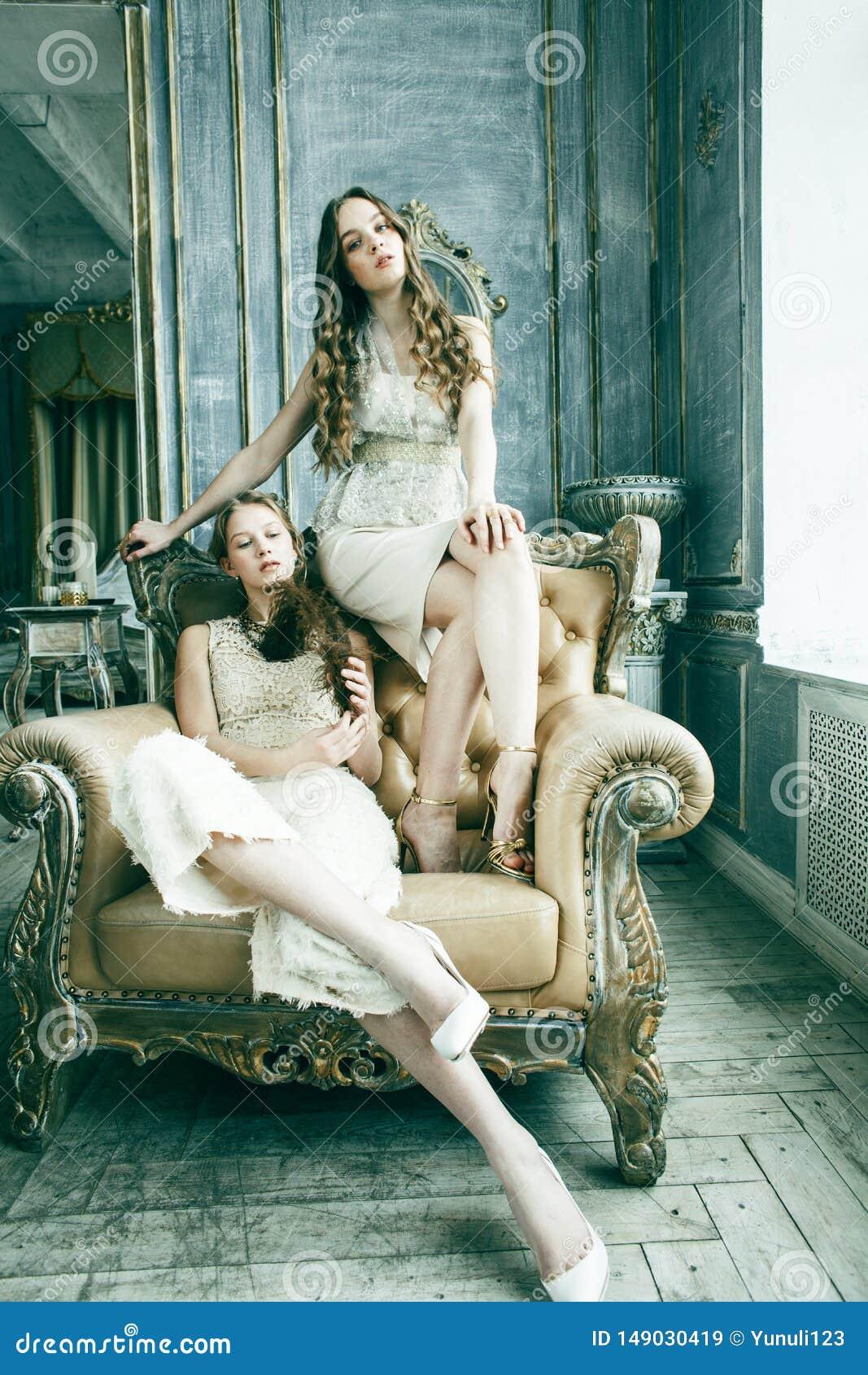 Ragazza riccia bionda dell acconciatura della sorella gemellata graziosa due nell interno di lusso della casa insieme, concetto r