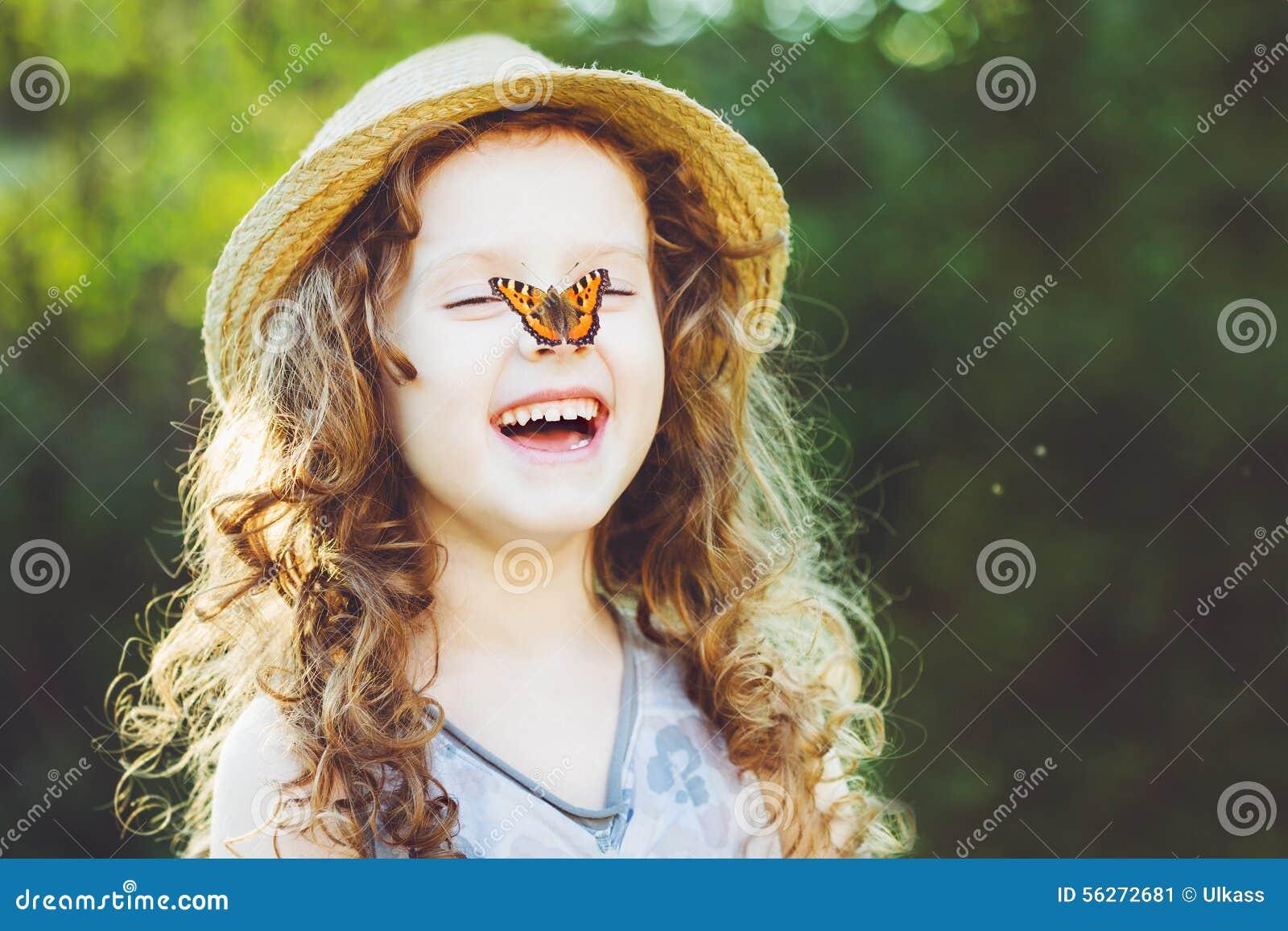 Ragazza riccia di risata con una farfalla sulla sua mano - Immagine di una ragazza a colori ...
