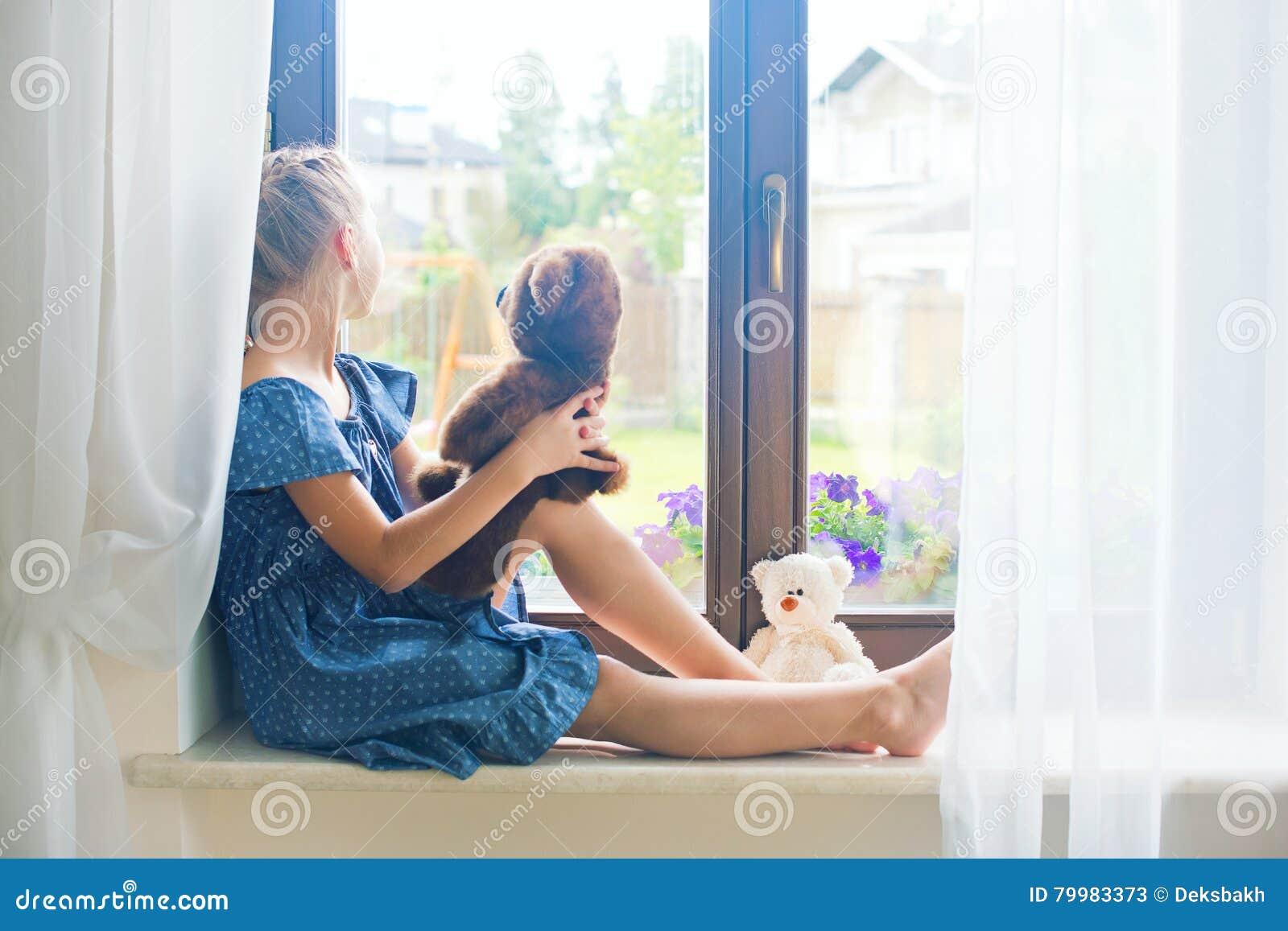 Ragazza russa del bambino solo che si siede vicino alla finestra a casa che gioca immagine stock - Finestra che non si chiude ...