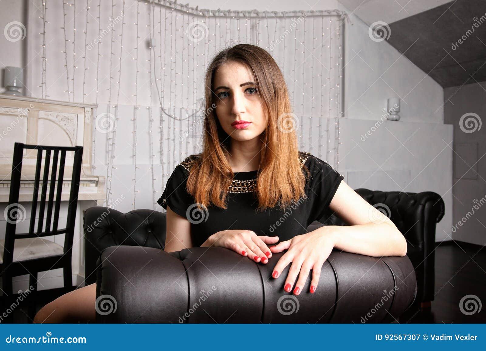 Ragazza sconosciuta attivamente nella ricerca messa in sedia di cuoio nera