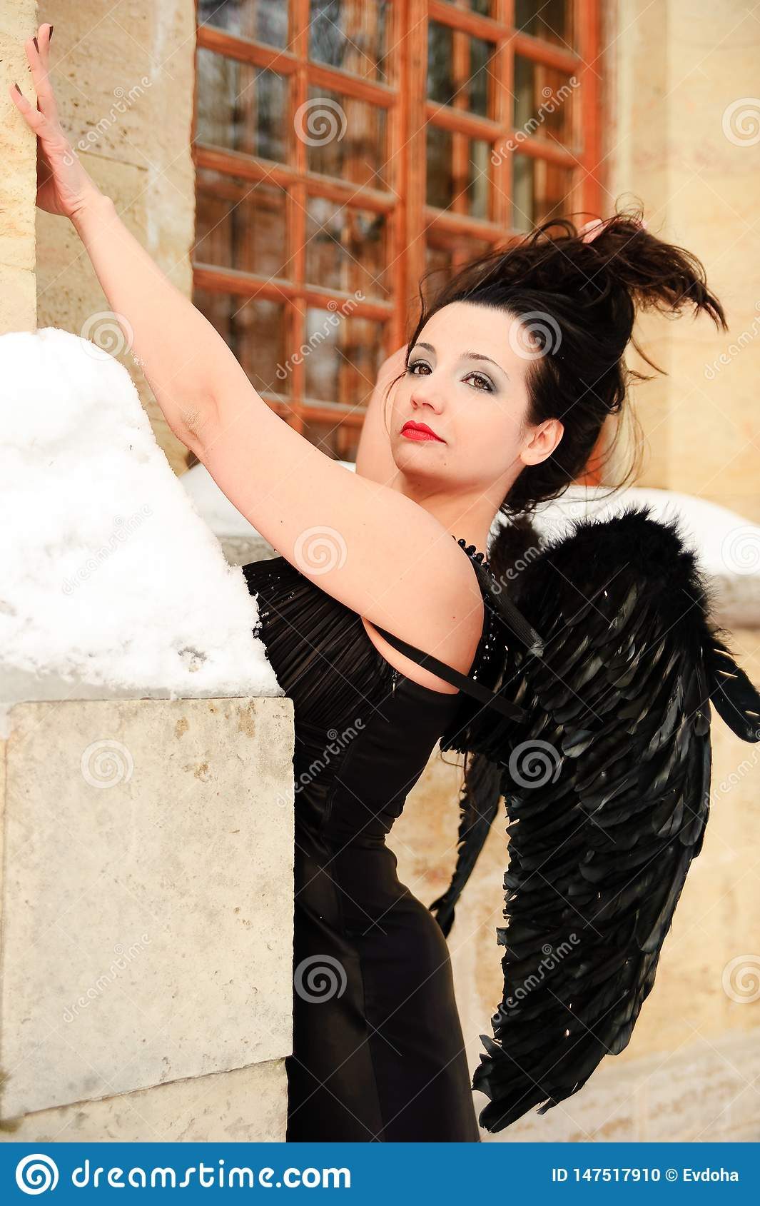 Ragazza sexy con le ali nere di angelo in un vestito nero