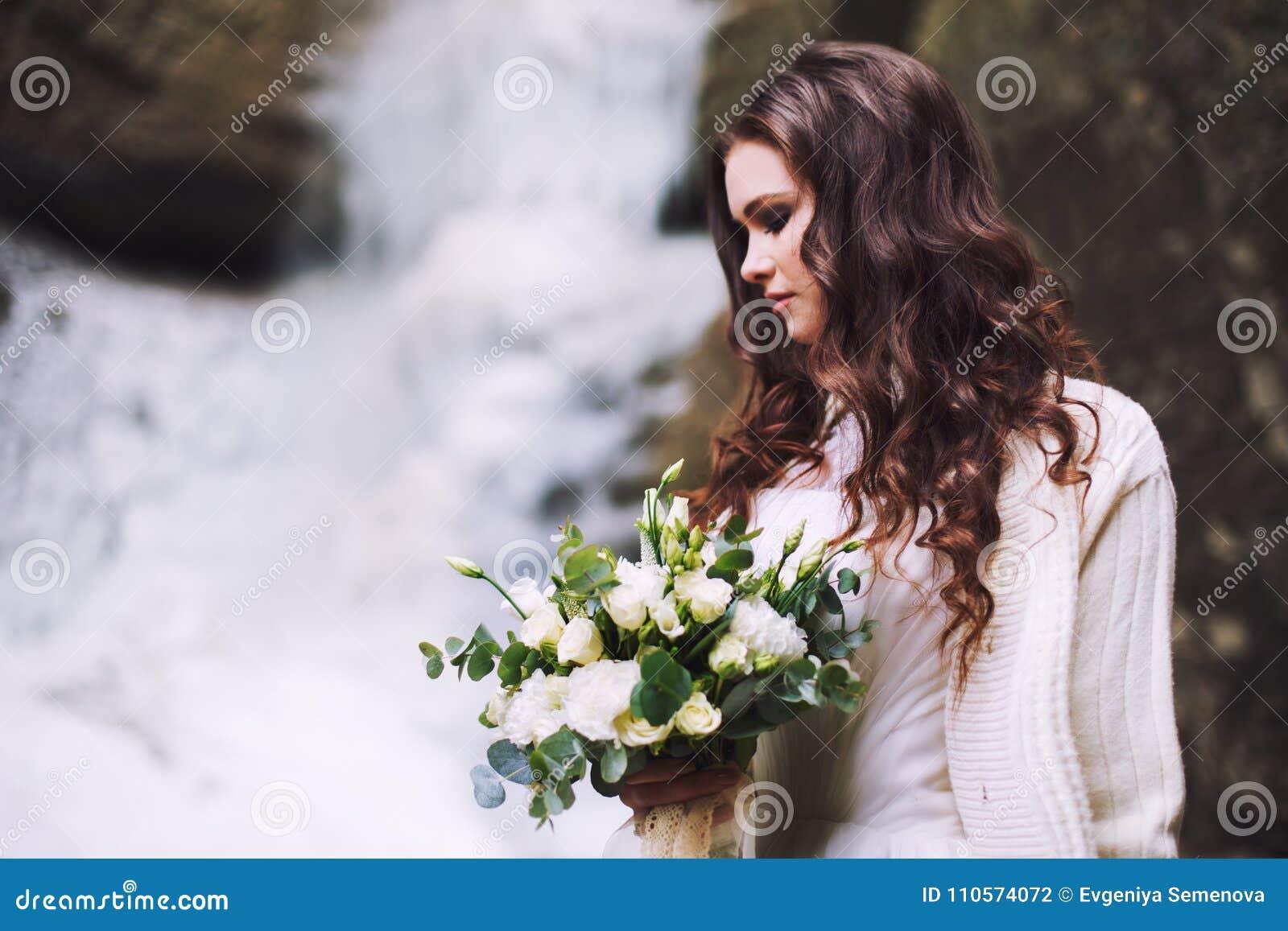 Ragazza sexy con un mazzo di nozze dei fiori contro lo sfondo di un ghiacciaio e delle montagne
