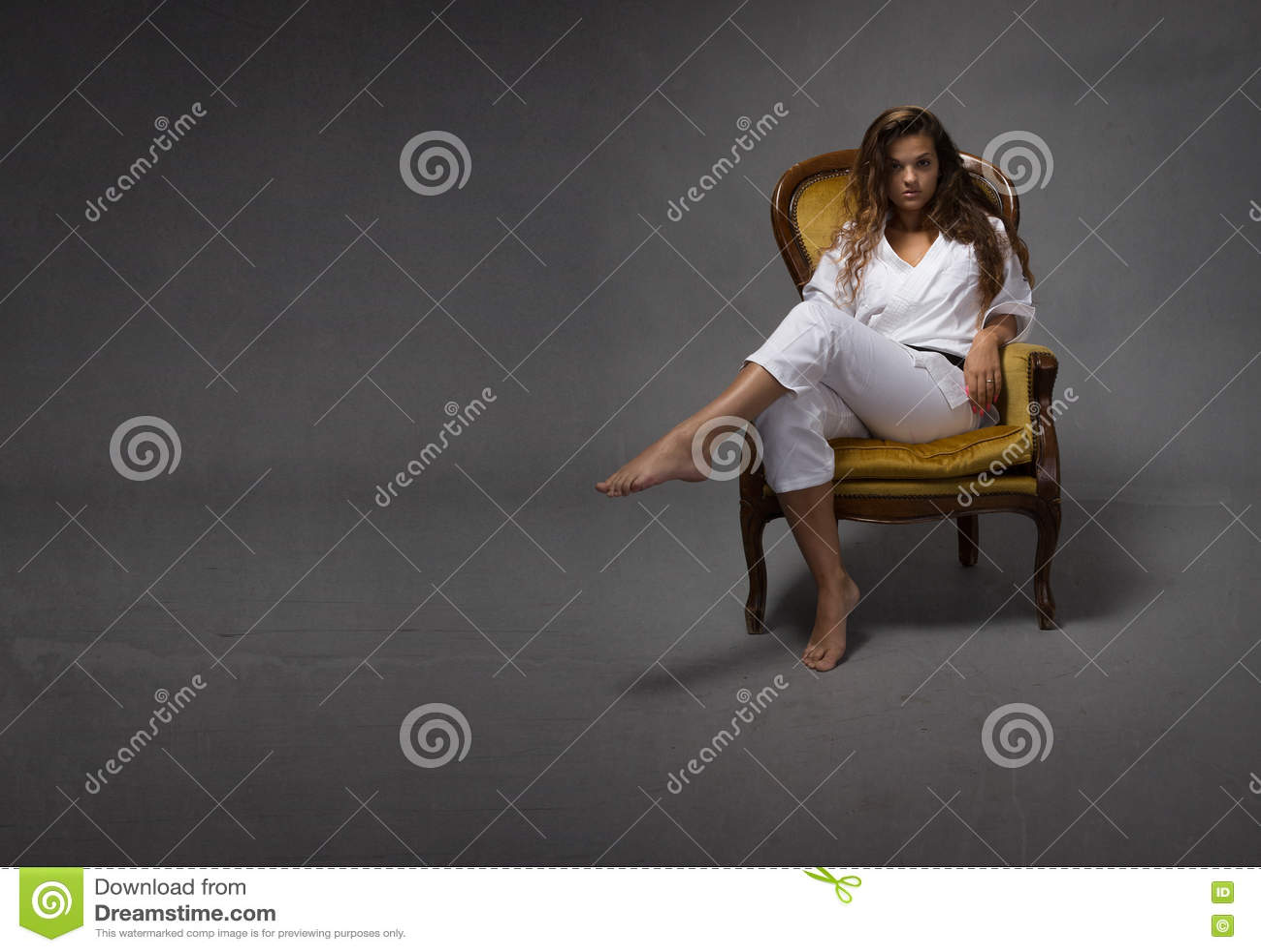 Ragazza sexy di karatè che si siede sul sofà
