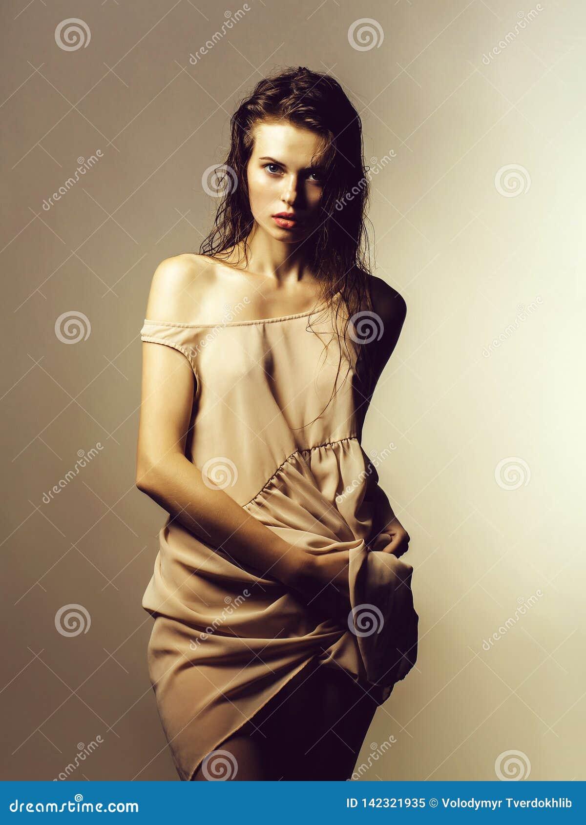 Ragazza sexy graziosa in vestito beige