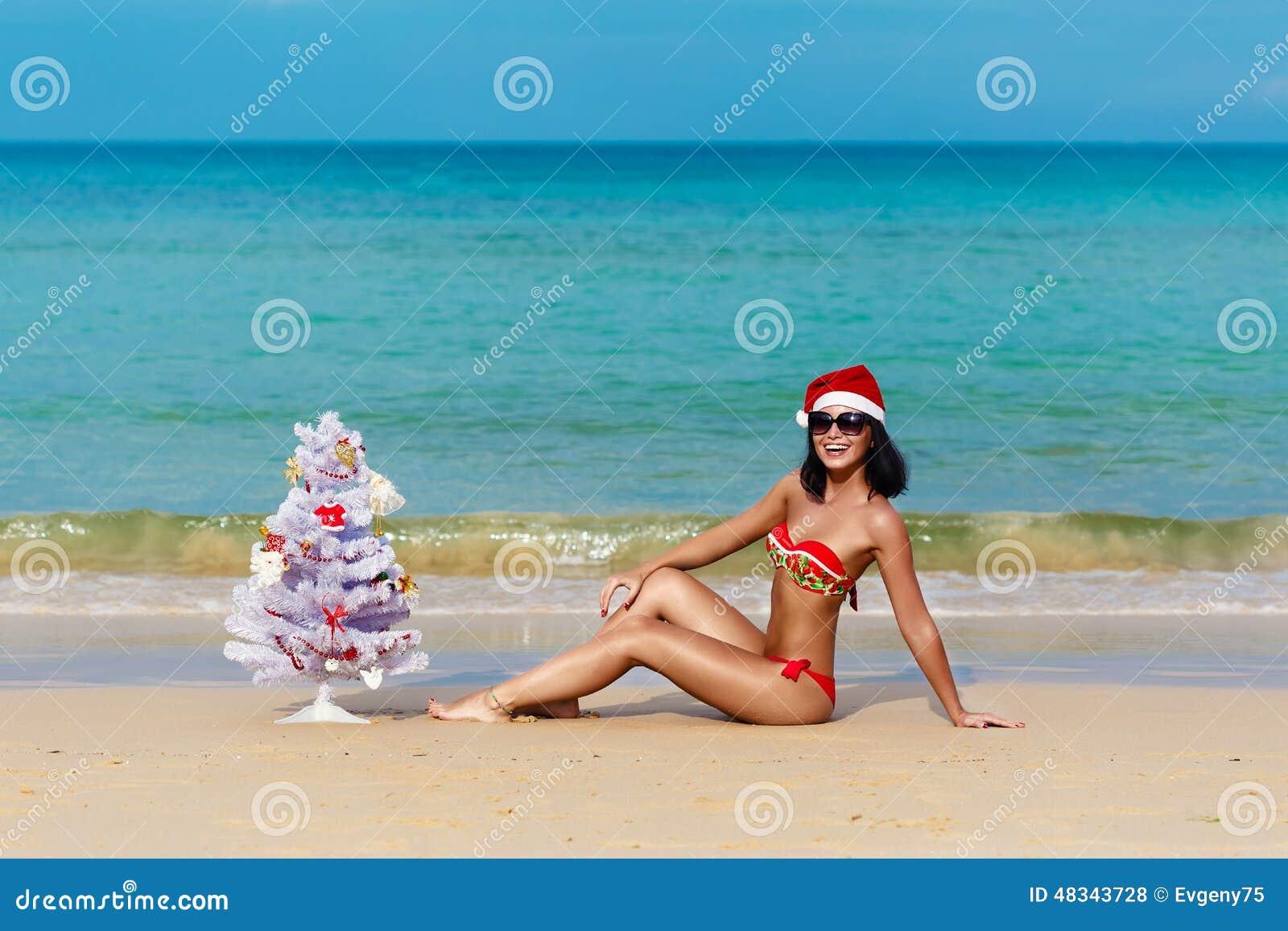 Ragazza sexy Santa in bikini su un abete della spiaggia