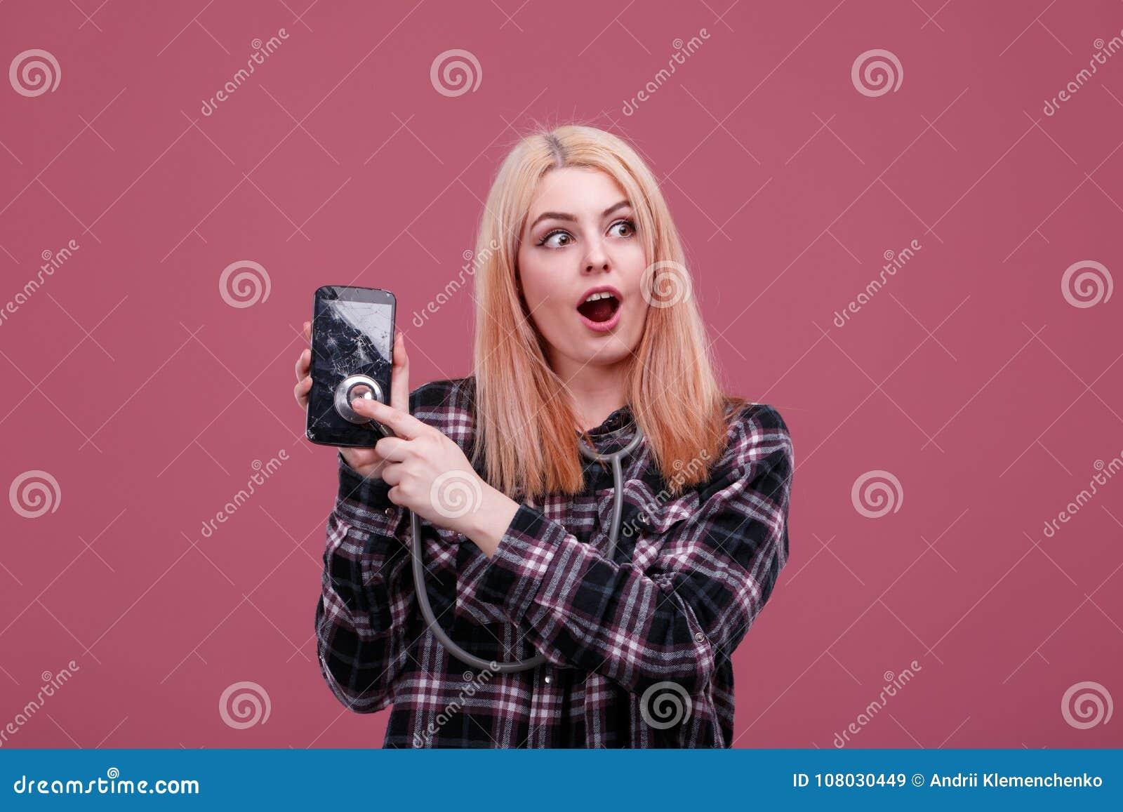 Ragazza sorpresa, ascoltante uno smartphone rotto con uno stetoscopio Su un fondo rosa