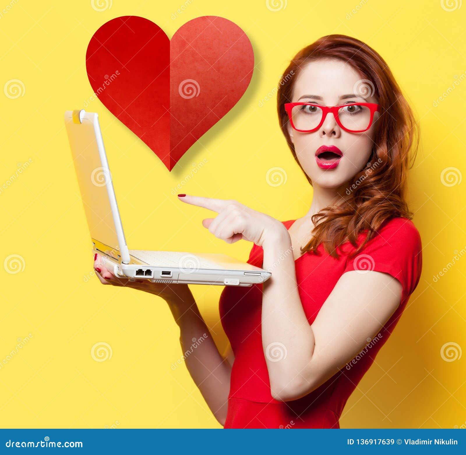 Ragazza sorpresa della testarossa con il computer portatile ed il cuore