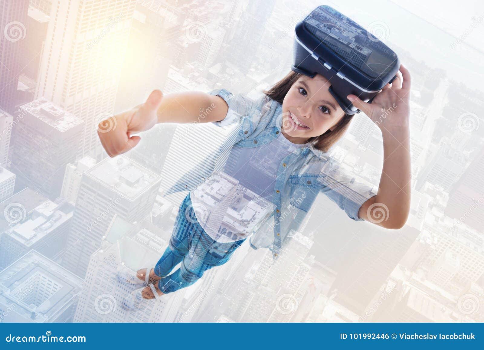 Ragazza sorridente che mostra i pollici su mentre rimuovendo la cuffia avricolare di VR