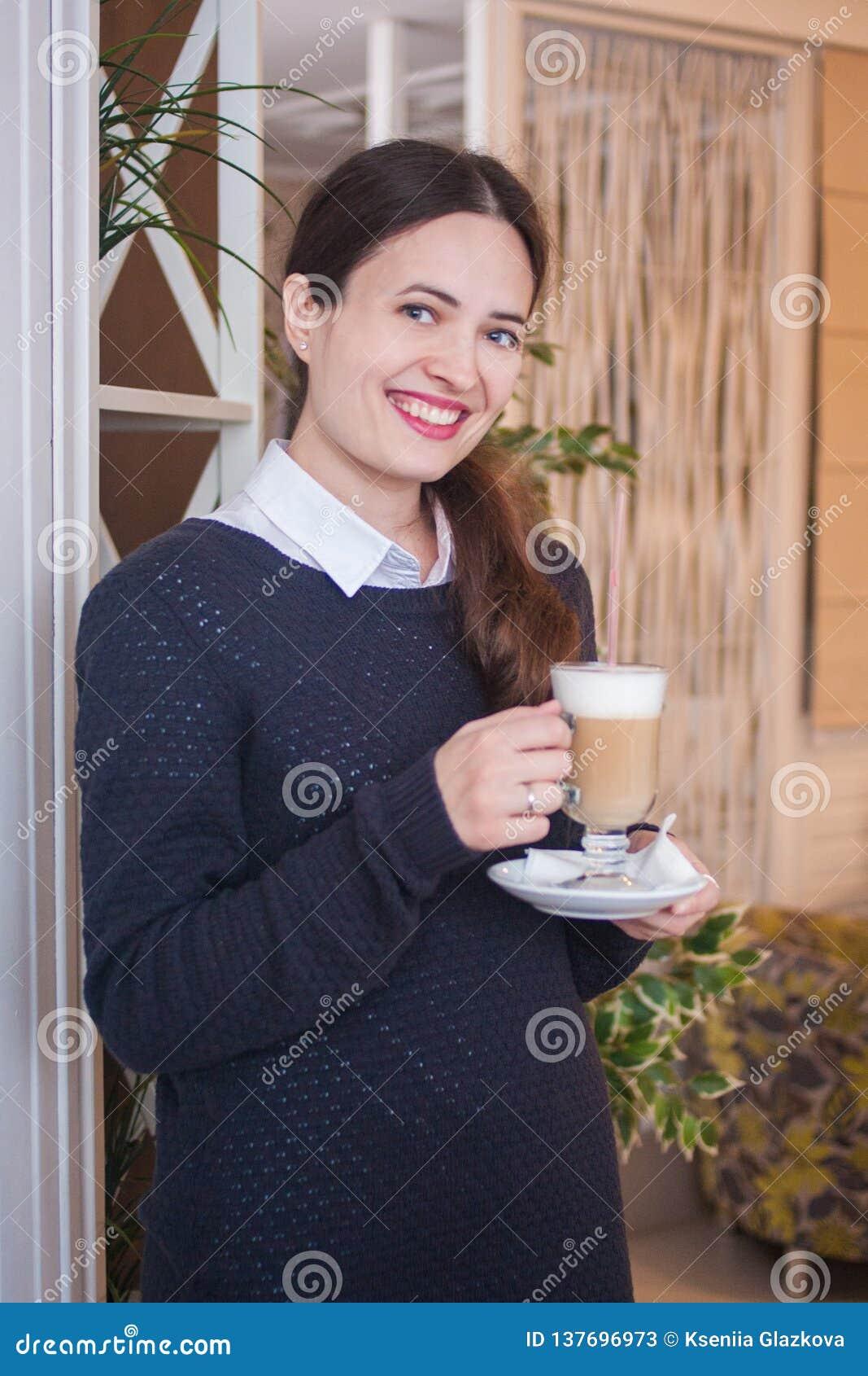 Ragazza sorridente con una tazza di cappuccino bewitching