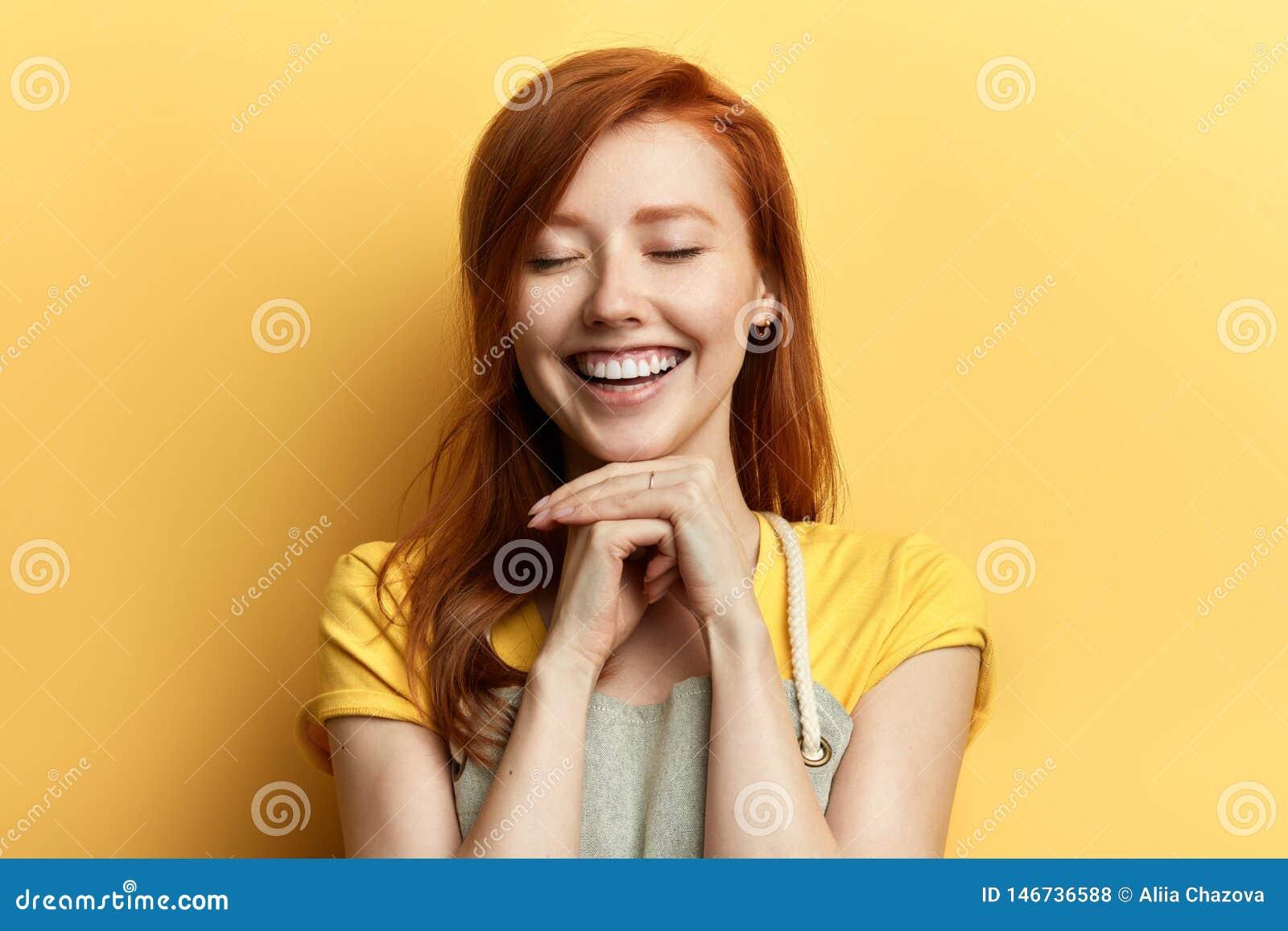 Ragazza splendida dello zenzero con gli occhi chiusi che ride di qualcuno