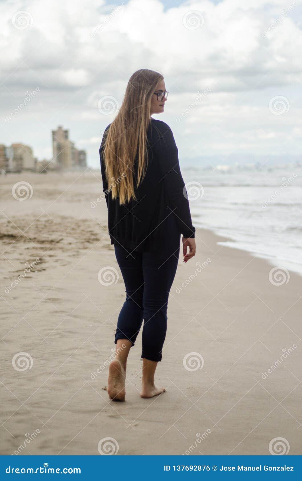 Ragazza sul suo indietro, camminando sulla spiaggia un giorno nuvoloso