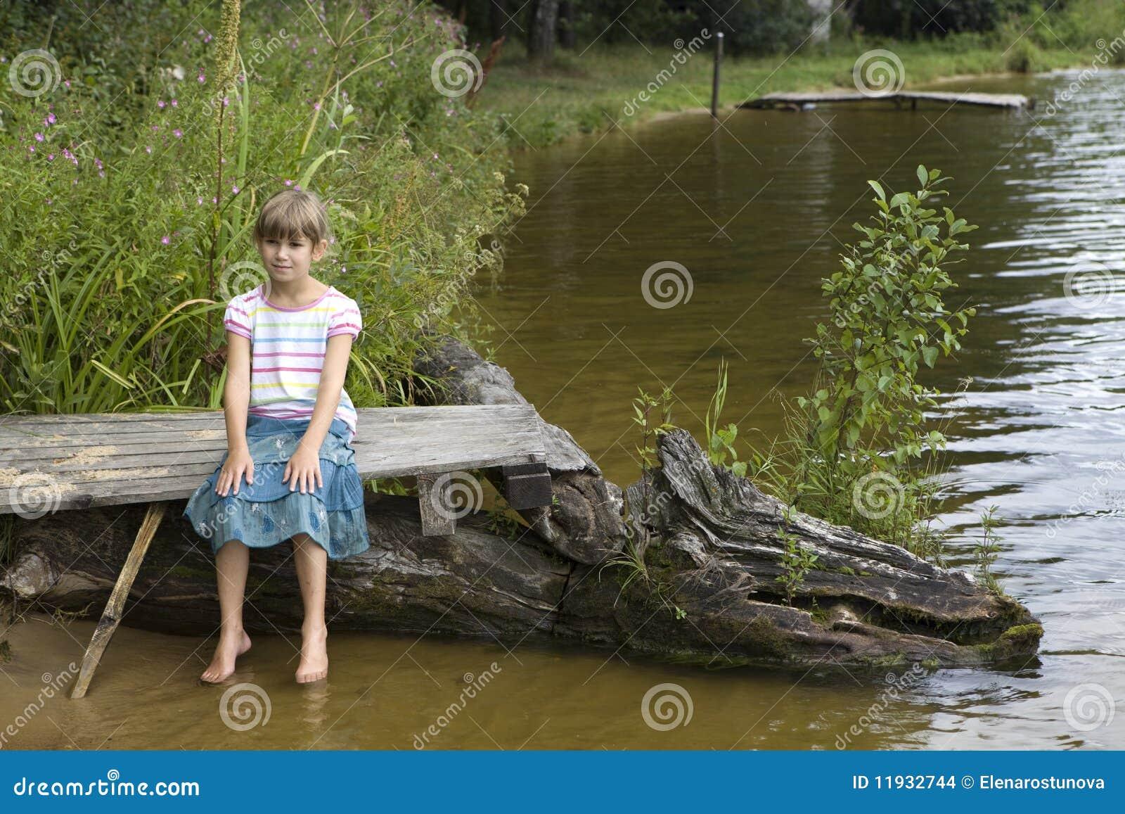 Stock: ragazza sveglia che si siede sul ponticello vicino al fiume