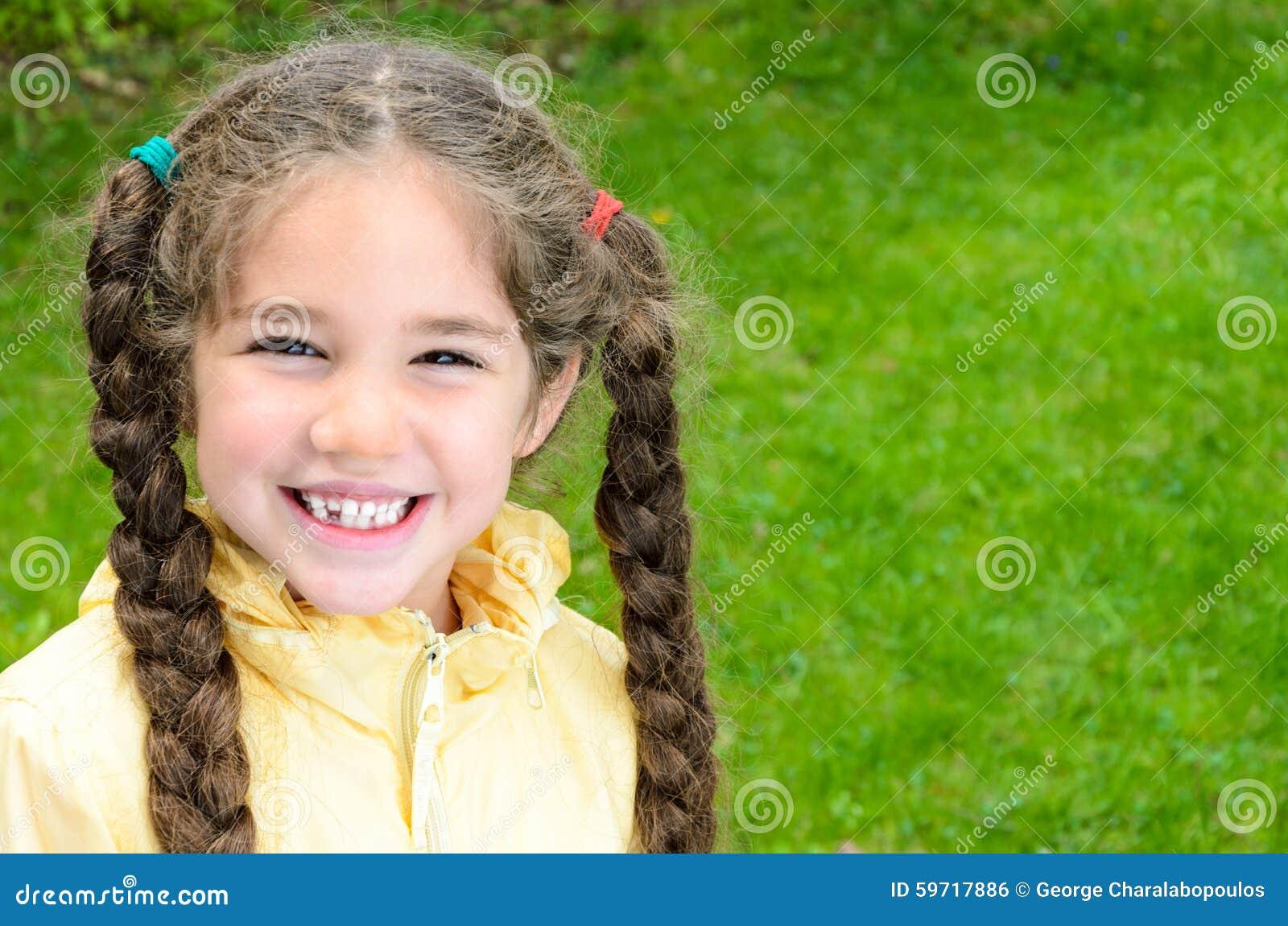 Ragazza sveglia con sorridere lungo delle trecce dei capelli