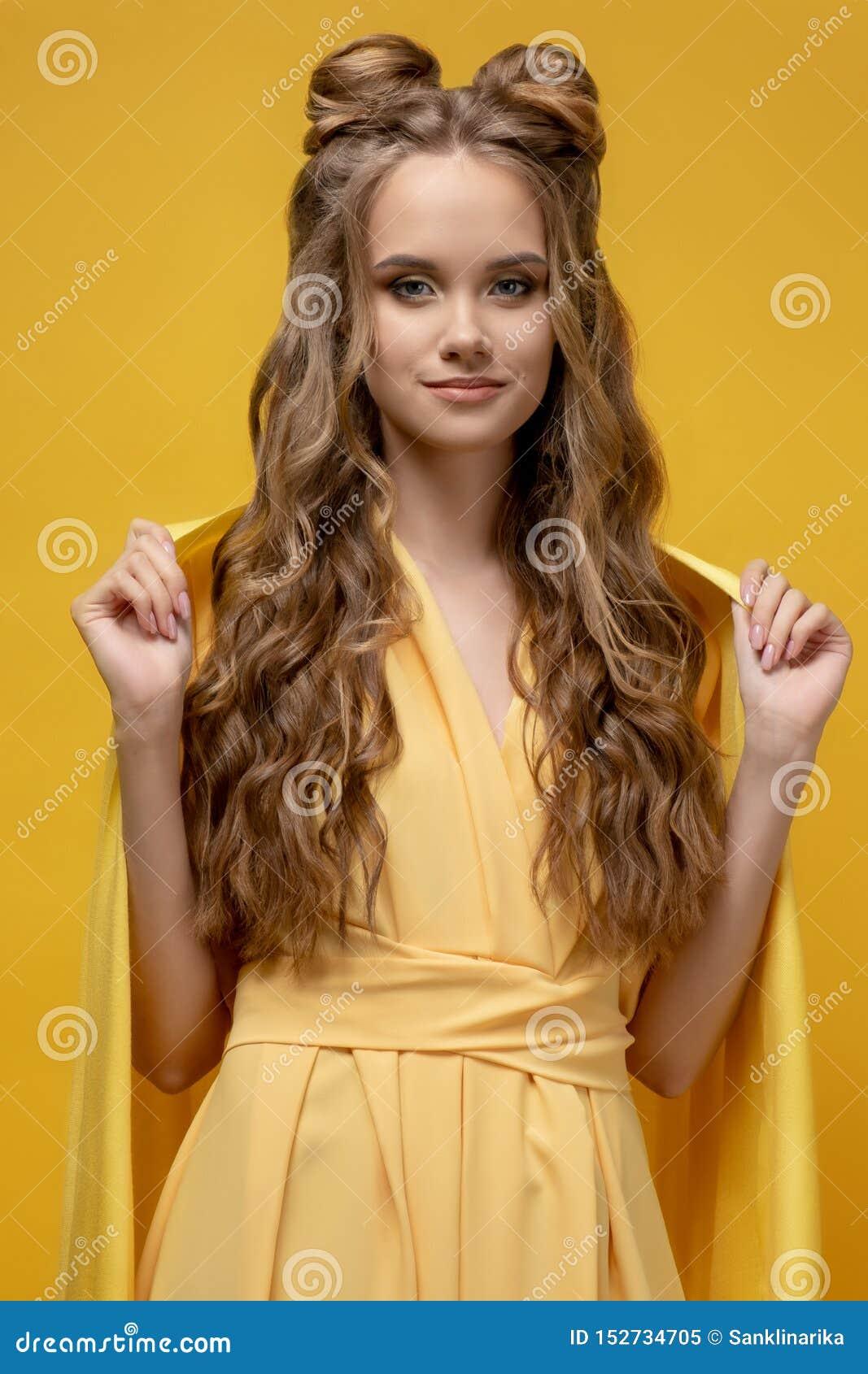 Ragazza sveglia in un vestito giallo su un fondo giallo con un taglio di capelli ed i capelli lunghi ricci