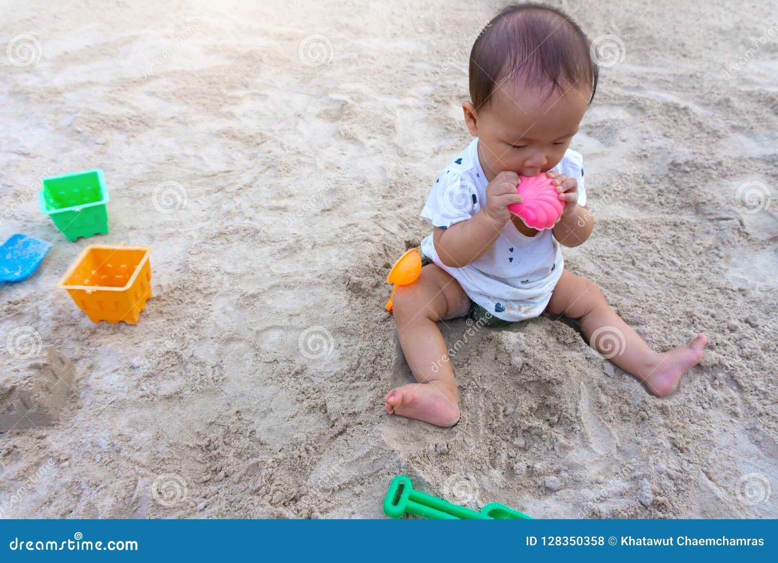 Ragazza tailandese del bambino asiatico del bambino che gioca con la sabbia